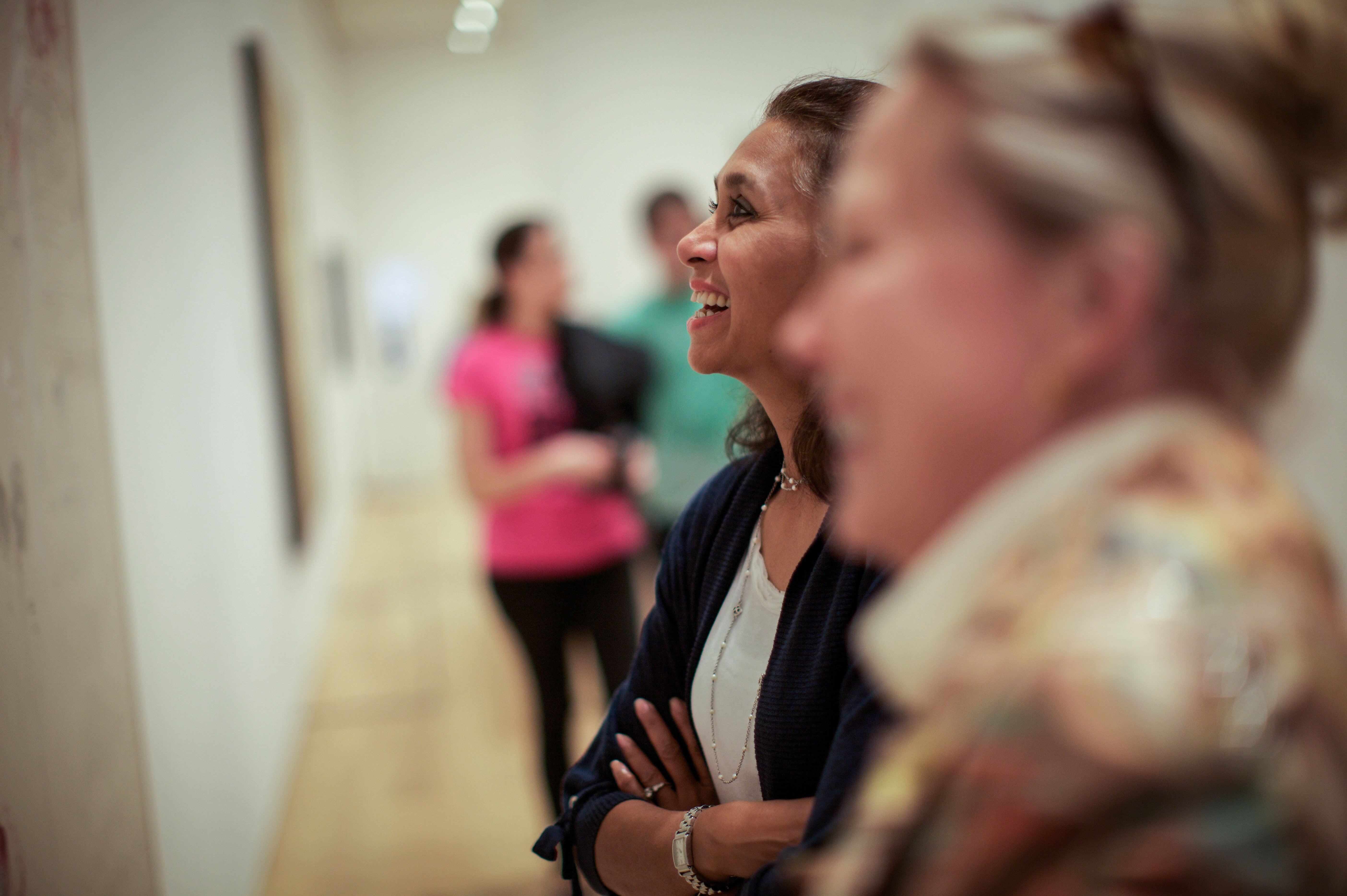 Two women stand in a gallery looking at art