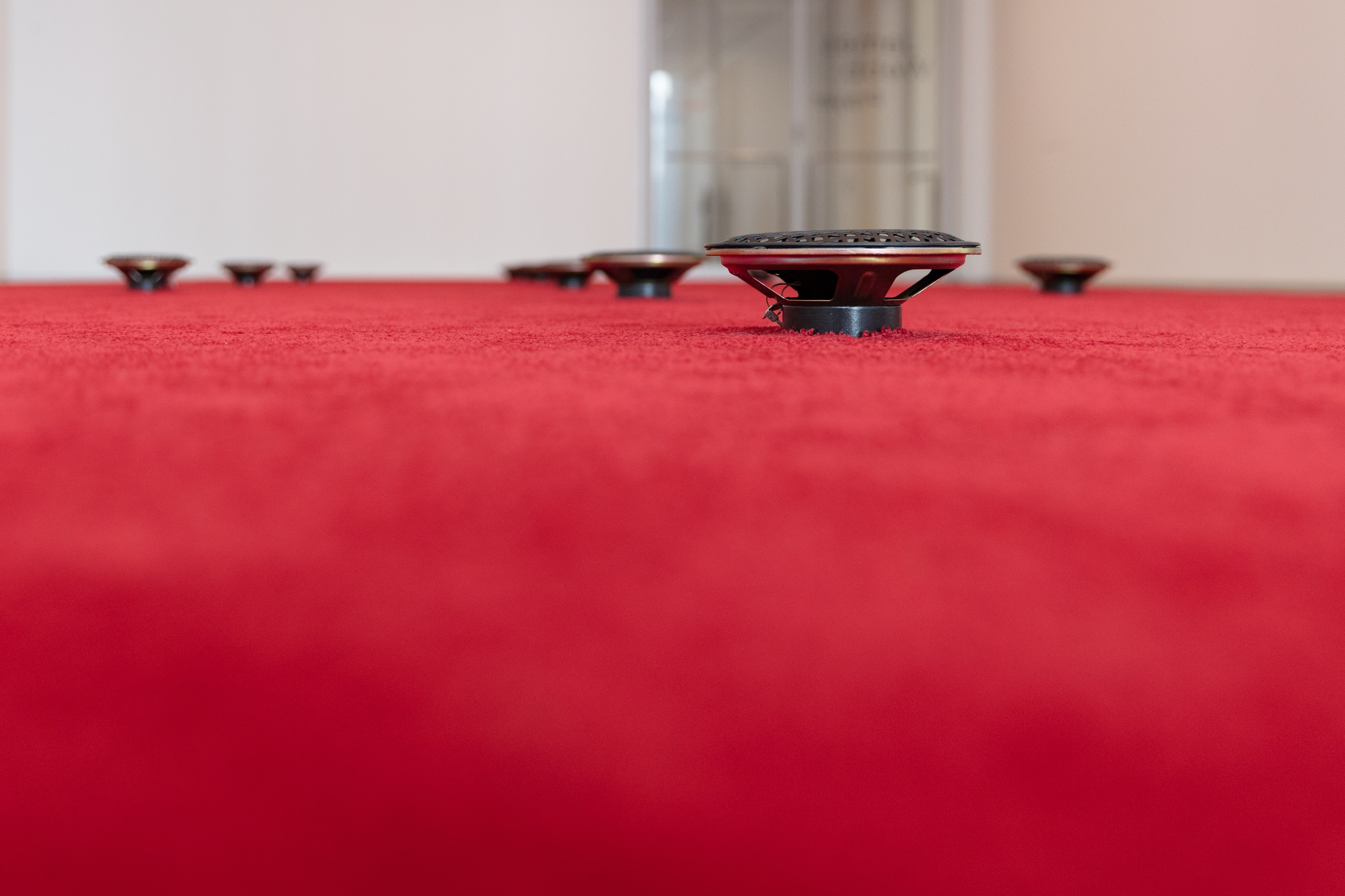 A close up photo of small black speakers on a red carpet.