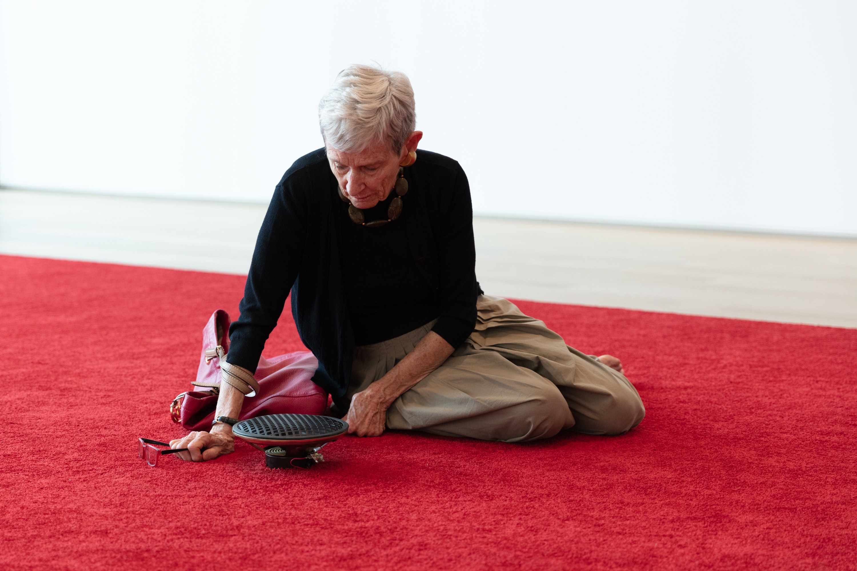 A photo of a person sitting on a red carpet listening to prayers emitting from a small black speaker.