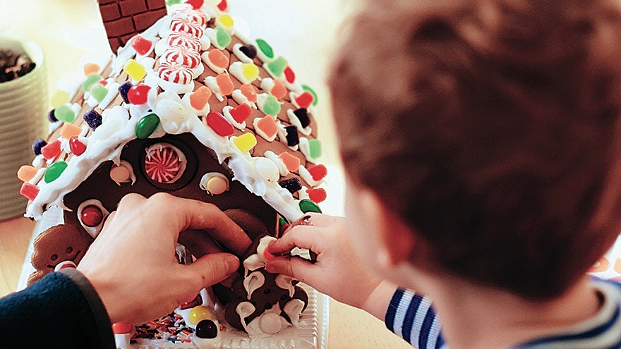 A boy decorates his gingerbread house.