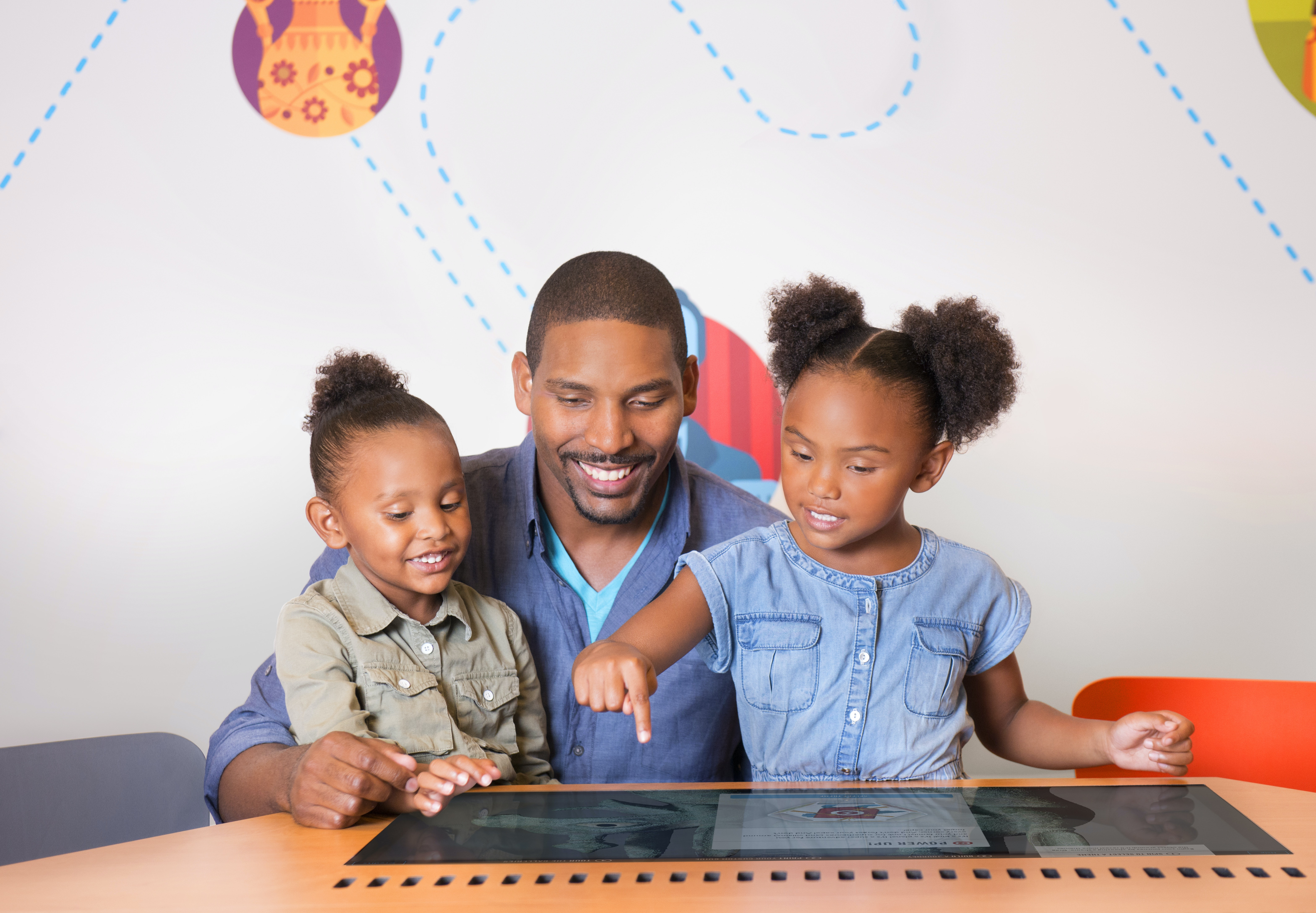 A family in the Ryan Learning Center playing with the JourneyMaker, an interactive touch screen