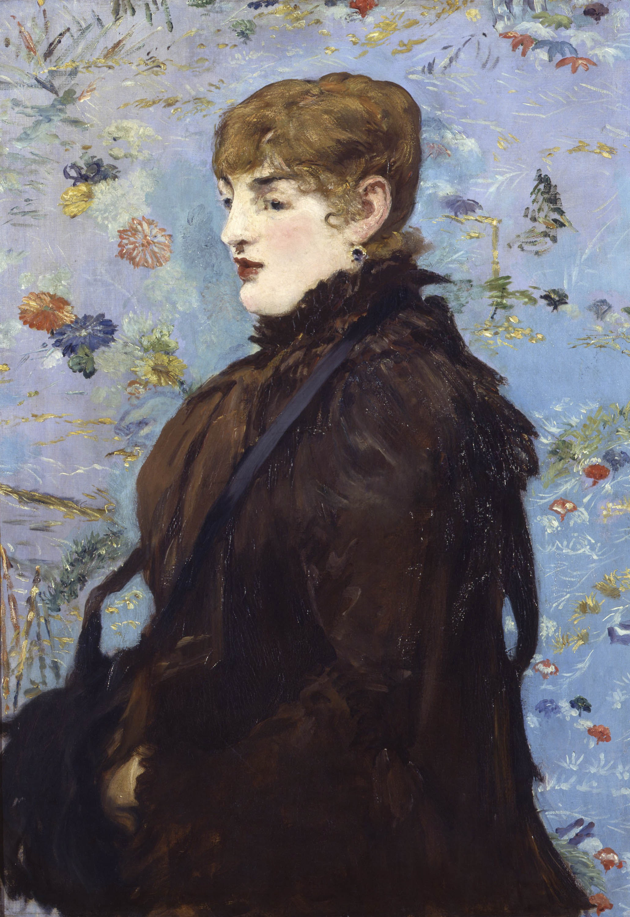 A woman in stylish black gown sits in three-quarters view against flowered wallpaper.