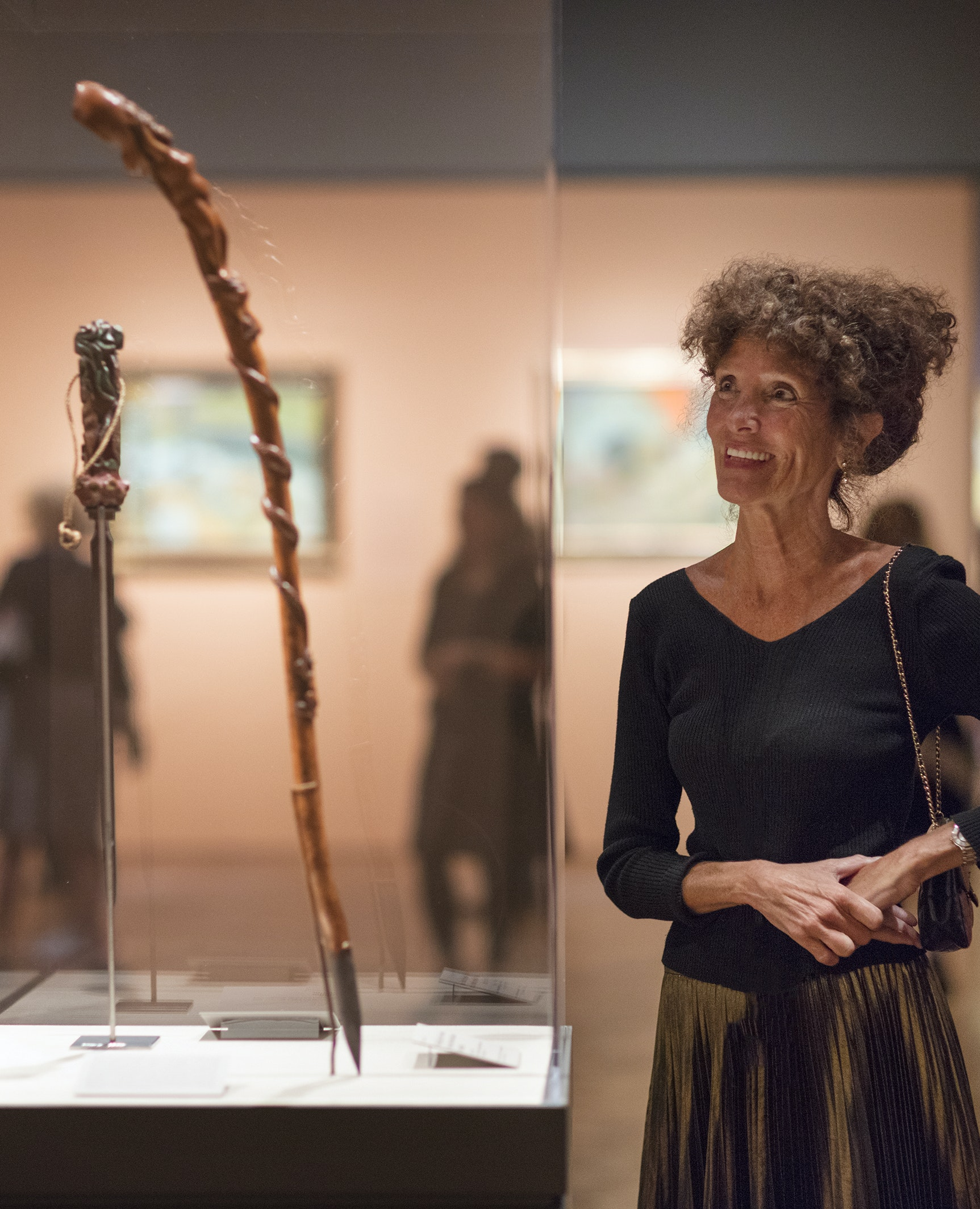 A photo of curator Gloria Groom dressed in a black shirt and green metallic skirt looking at an object in a glass case.