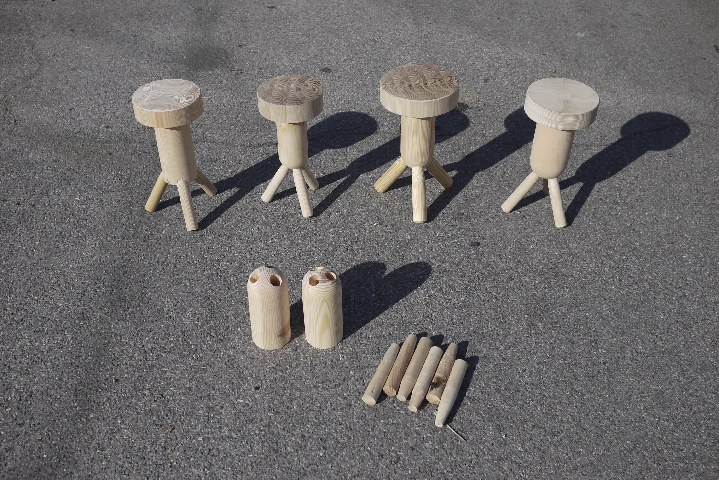 A photo of prototypes for small wooden stools designed by Max Lamb. The pieces of the prototypes are laid out on concrete in bright sunlight.