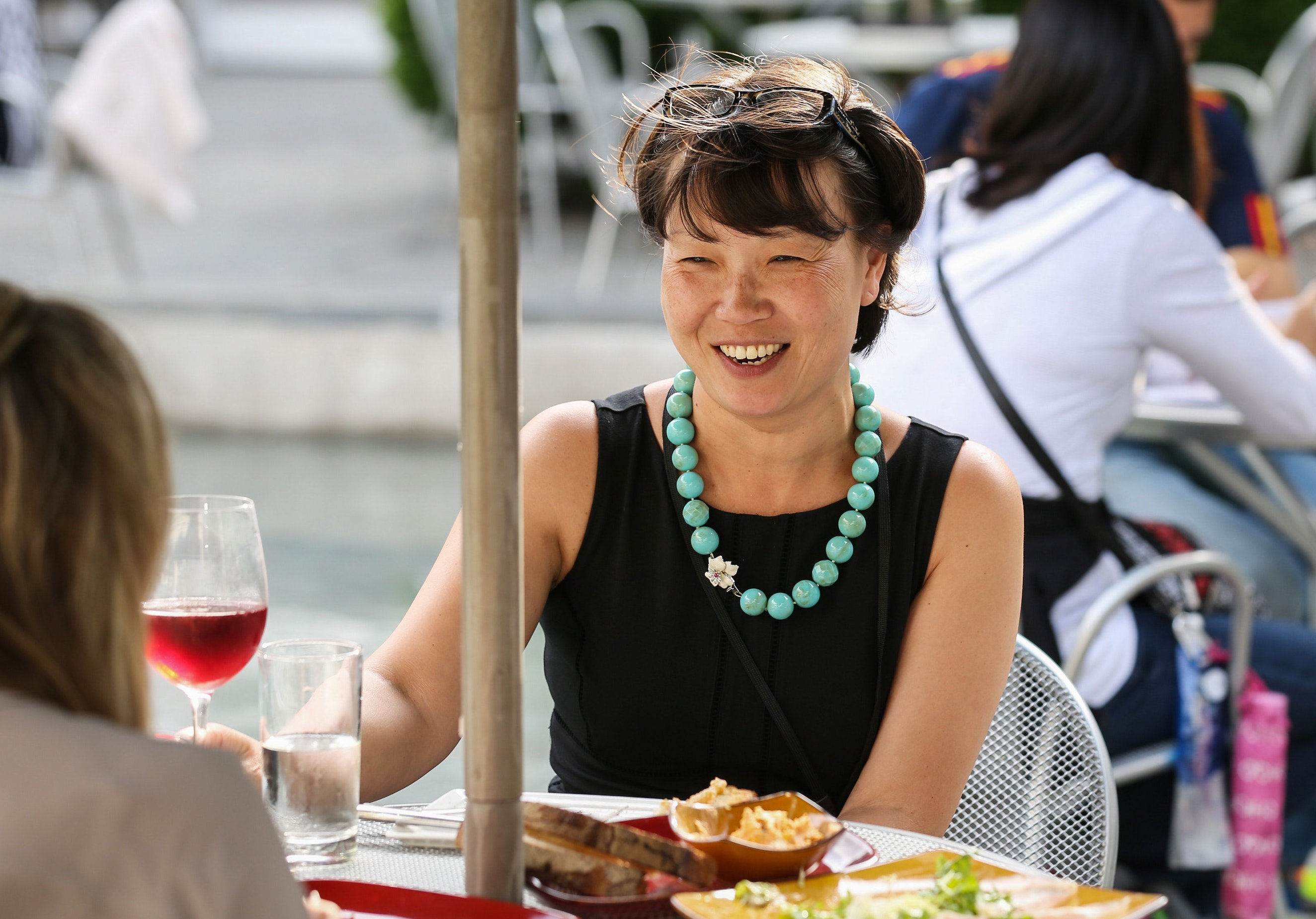 A woman in a black dress enjoys a glass of wine outside.