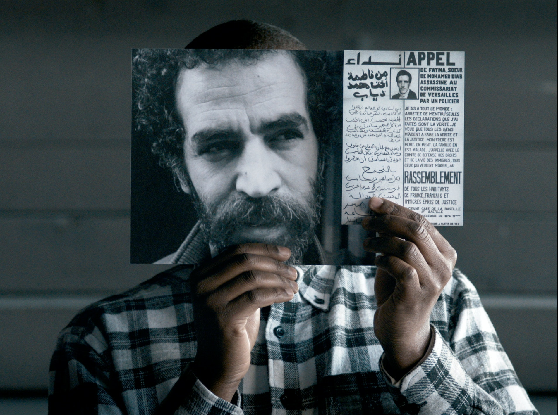 A man seen from the shoulders up holds a photograph of a man's face in front of his own as weel as
