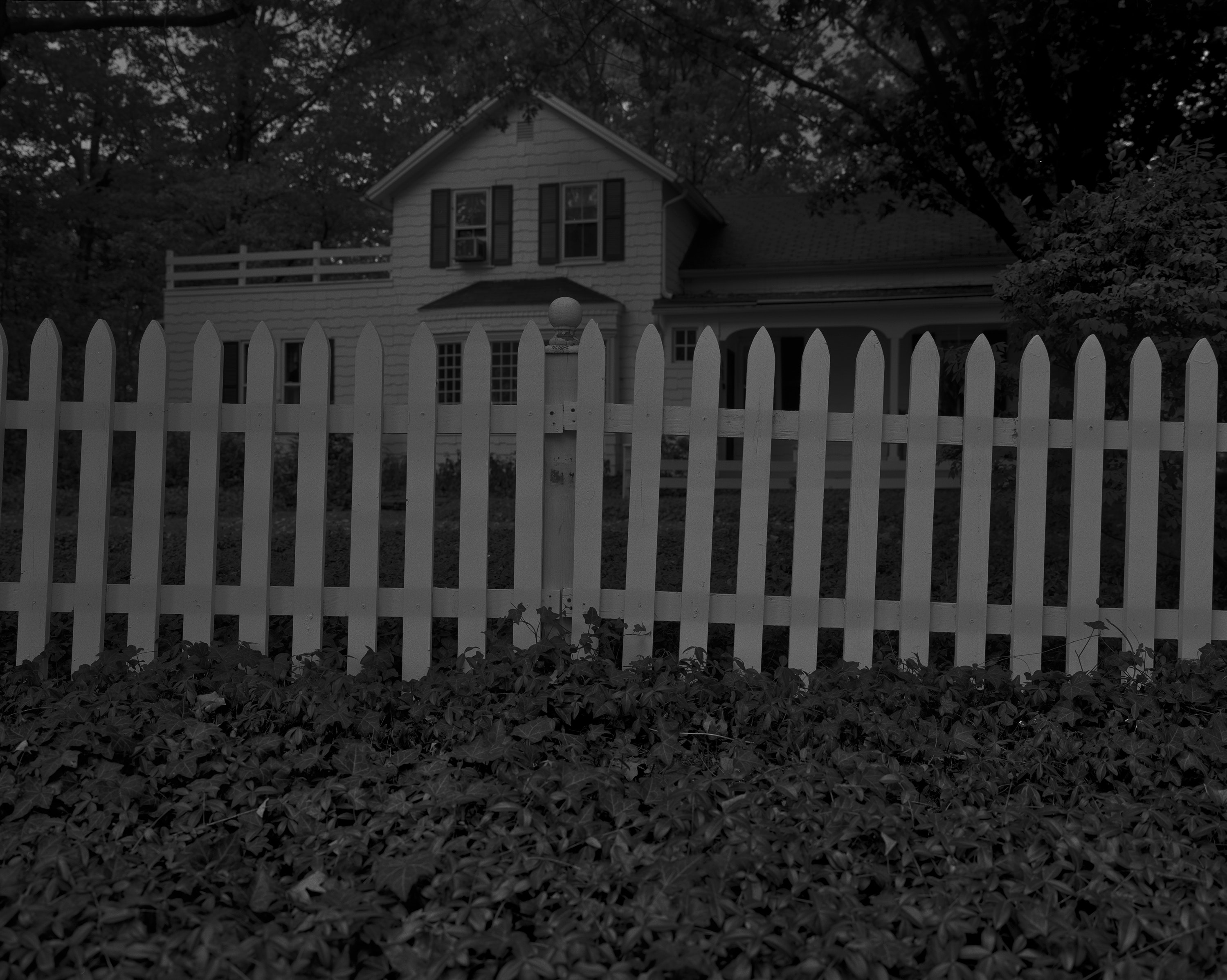 A black-and-white photograph shows a white house guarded by a white picket fence at night.