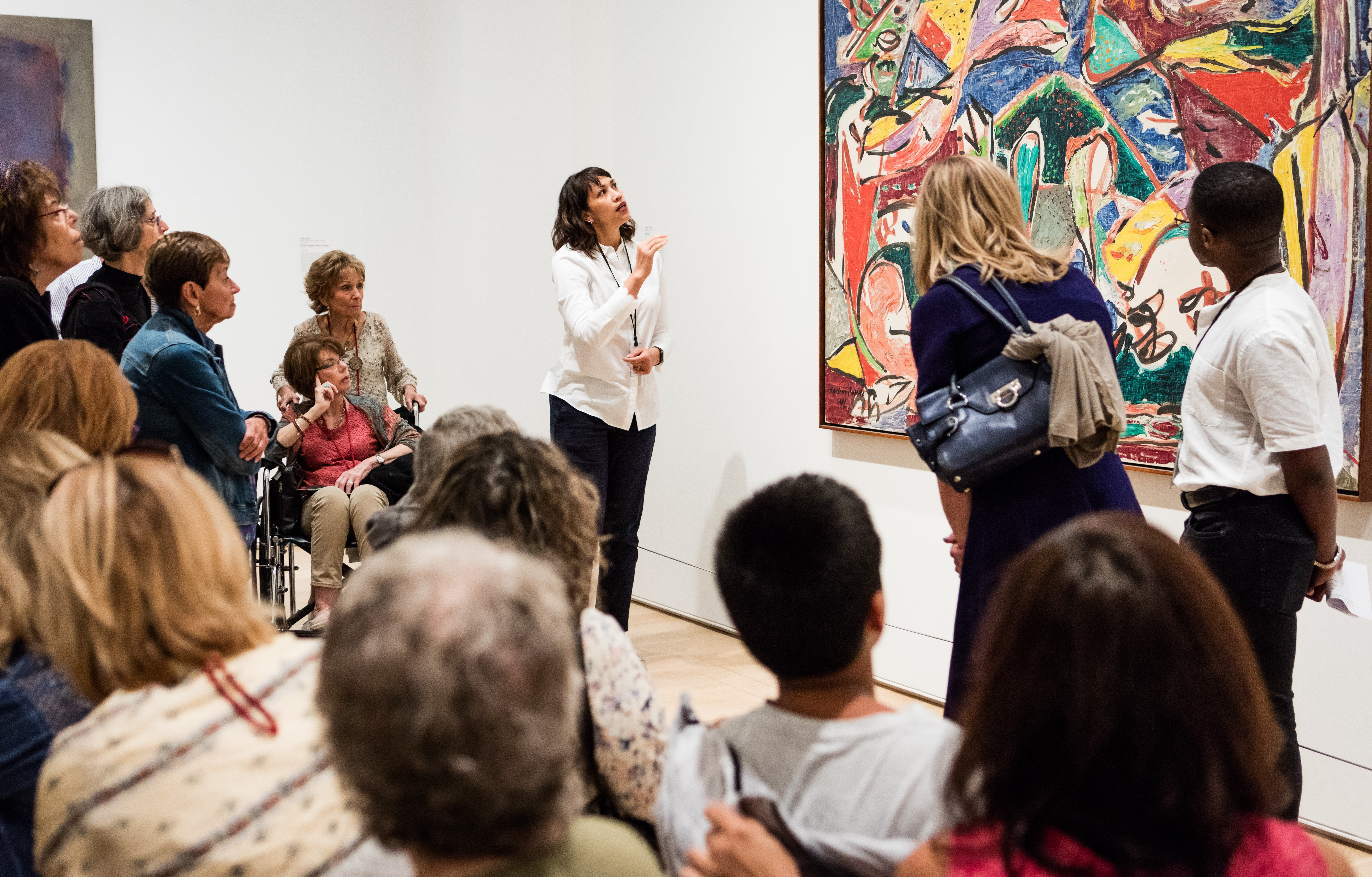 A staff person speaks about a modern painting in front of a large group of people.