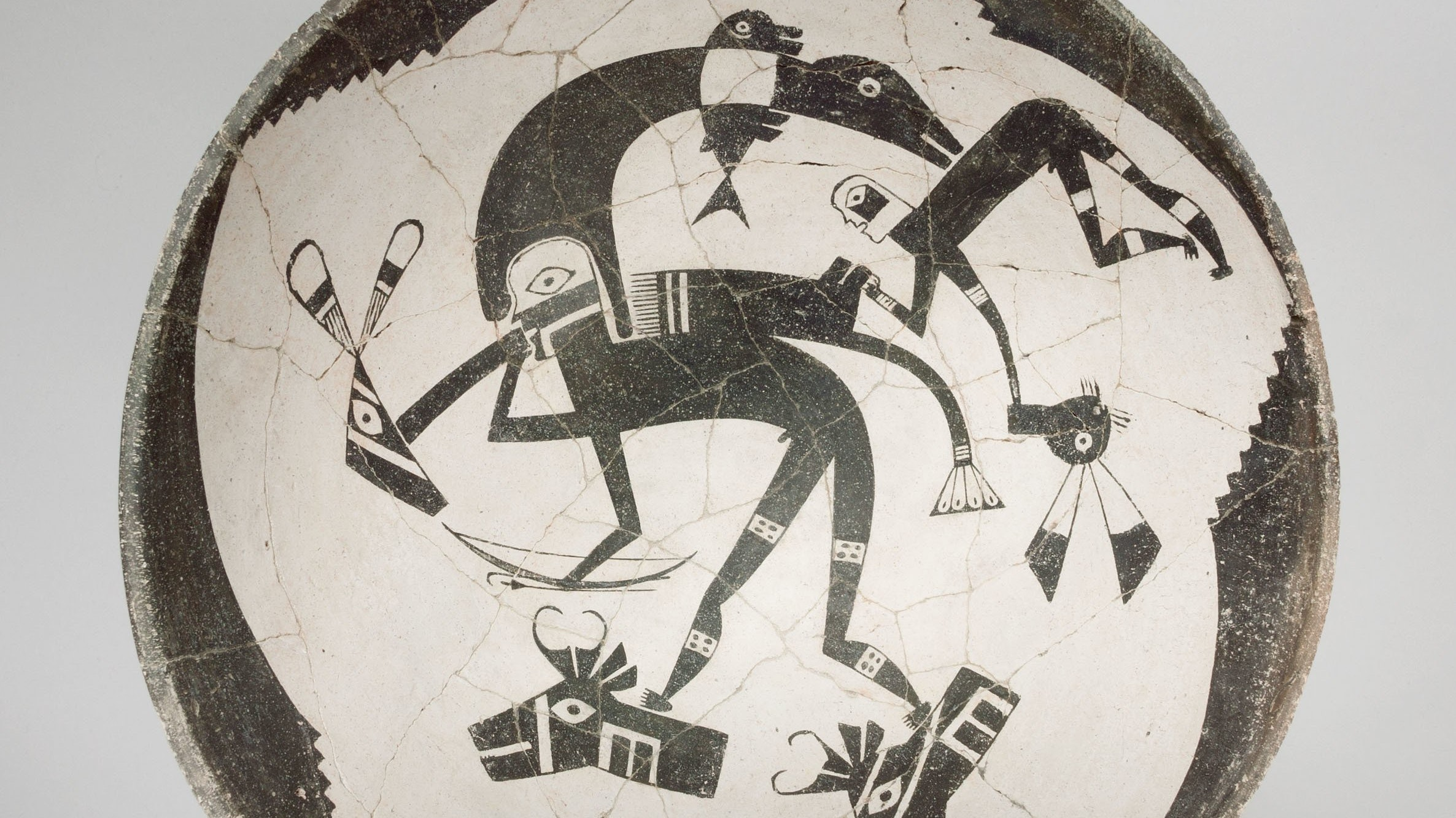 The interior of a ceramic bowl is painted in black-and-white showing a human figure with a bow and arrow and heron headress interacting with what appear to be the decapitated heads of animals.