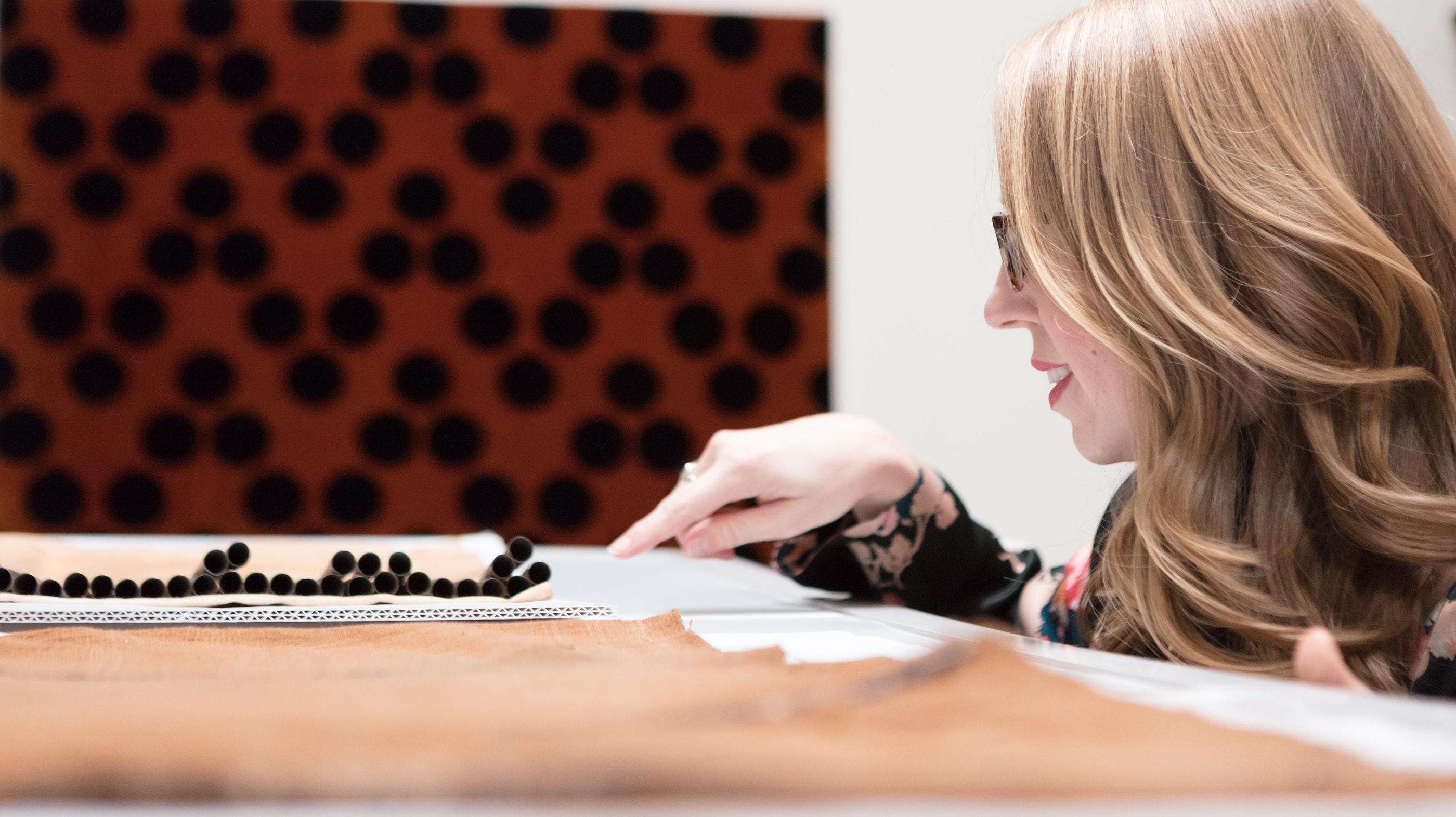Curator Erica Warren examines a textile