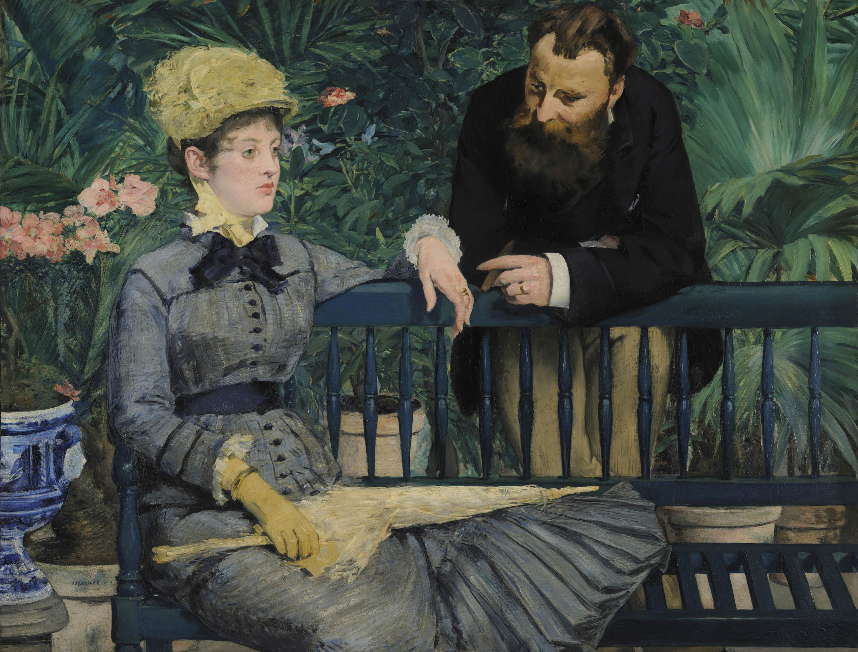 A couple on a park bench, the stylish young woman sits staring stright ahead while the main leans over the back looking toward her.