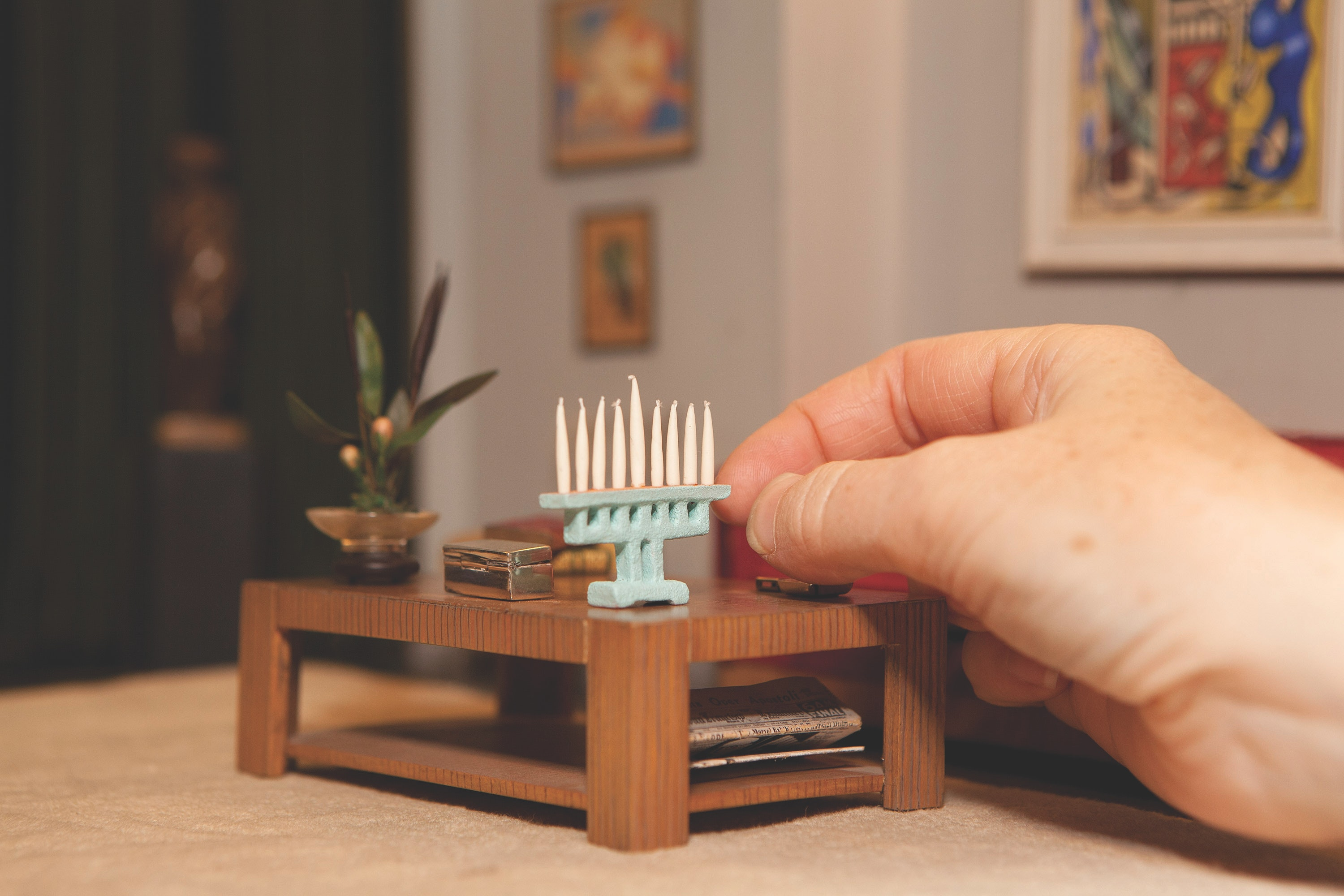 A photo of a miniature menorah being placed on a table inside one of the Thorne Rooms.