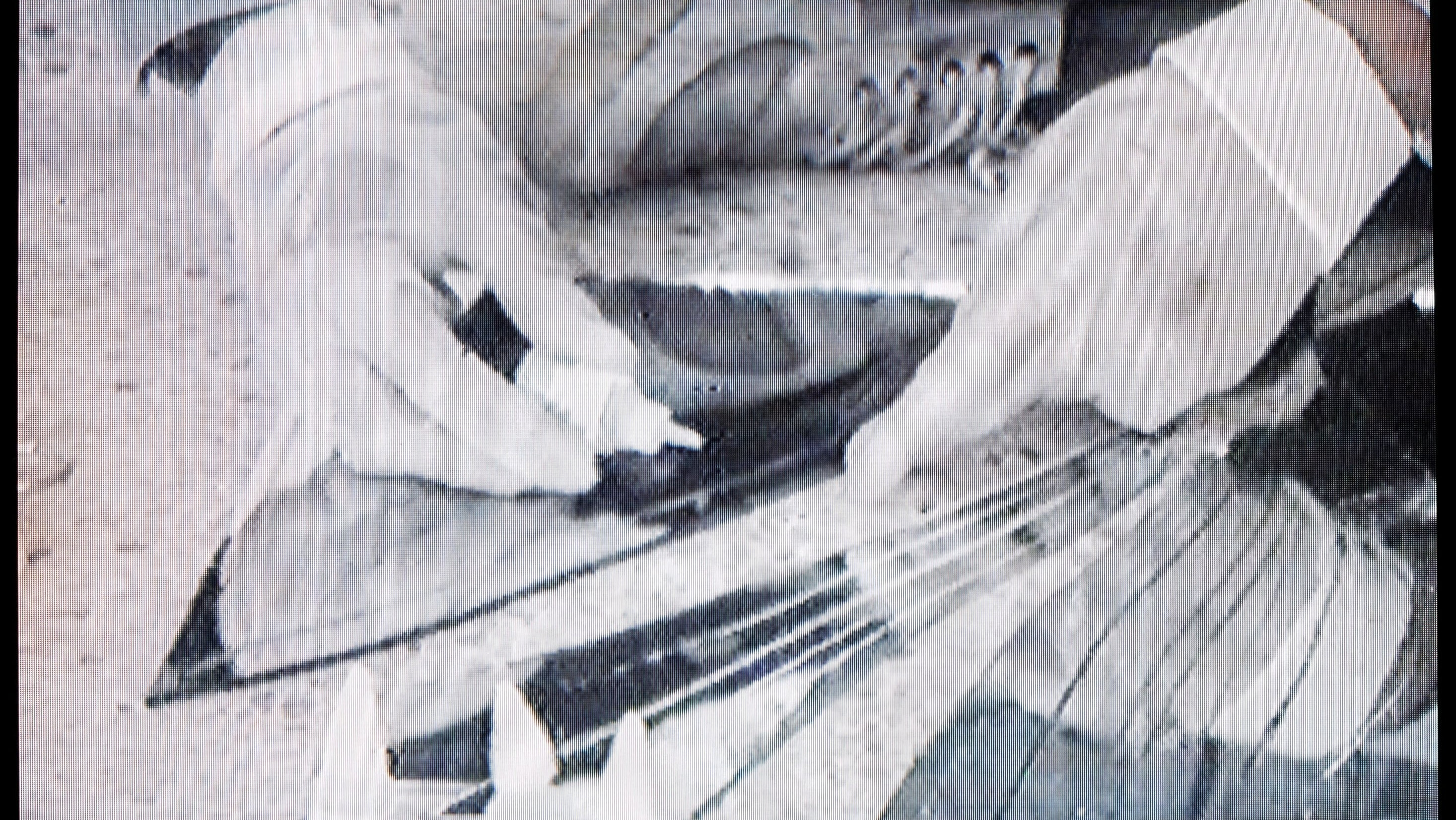 A still from a film that shows a close up of a person's hands as they glue a mirror together.
