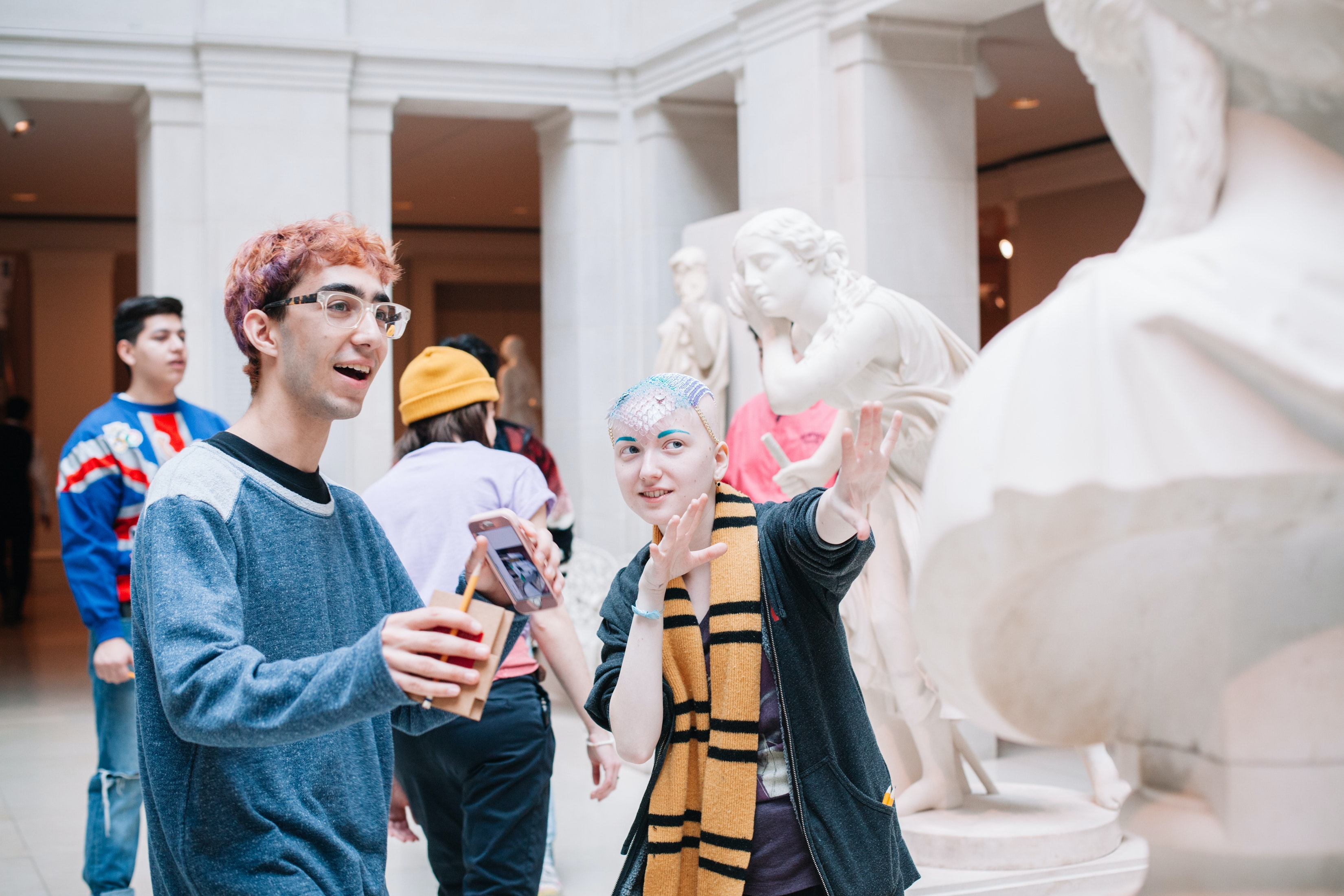 Two teens have a spirited conversation in the American sculpture gallery.