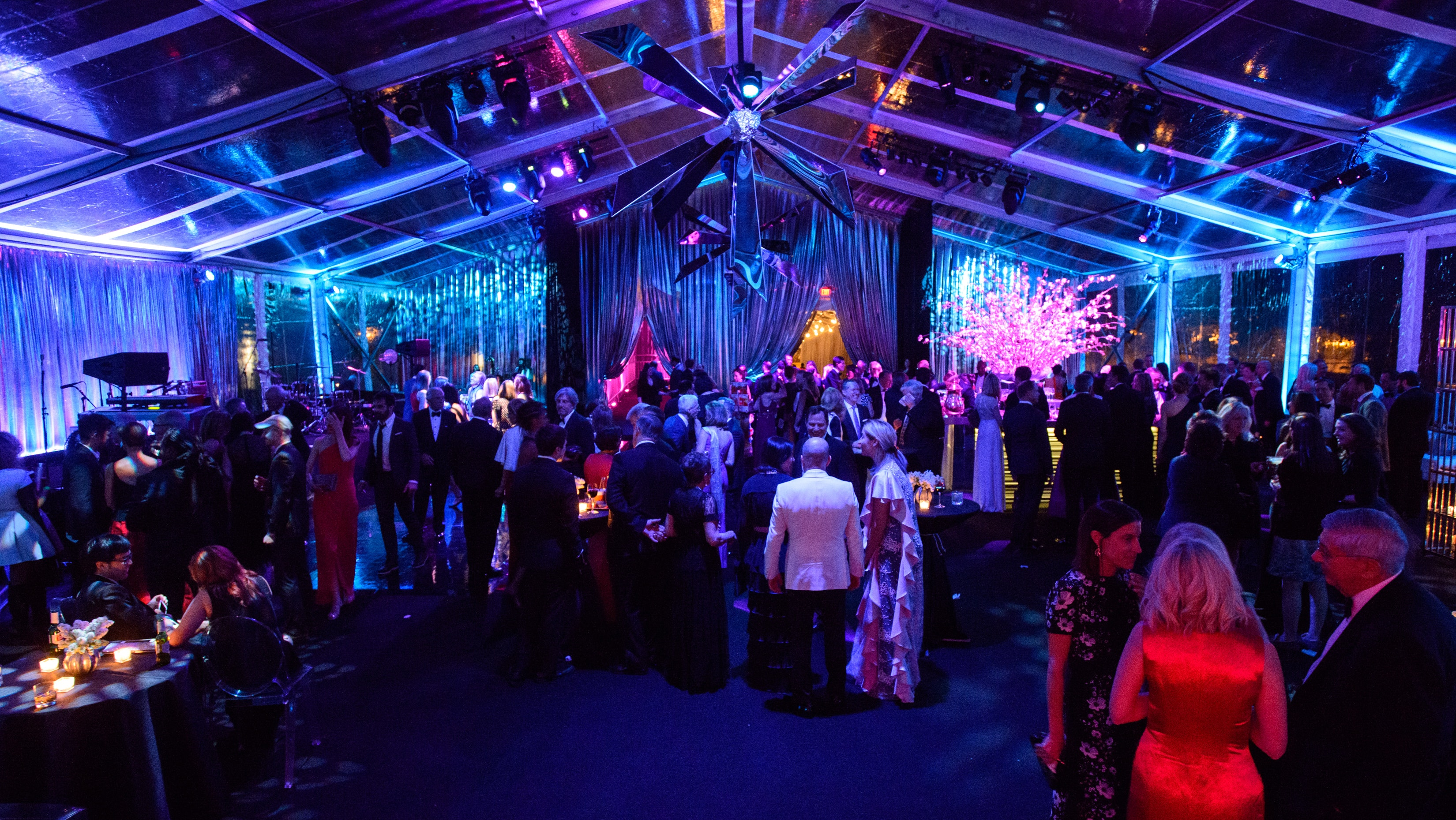 Guests dance in a large tented space filled with multi-colored light.