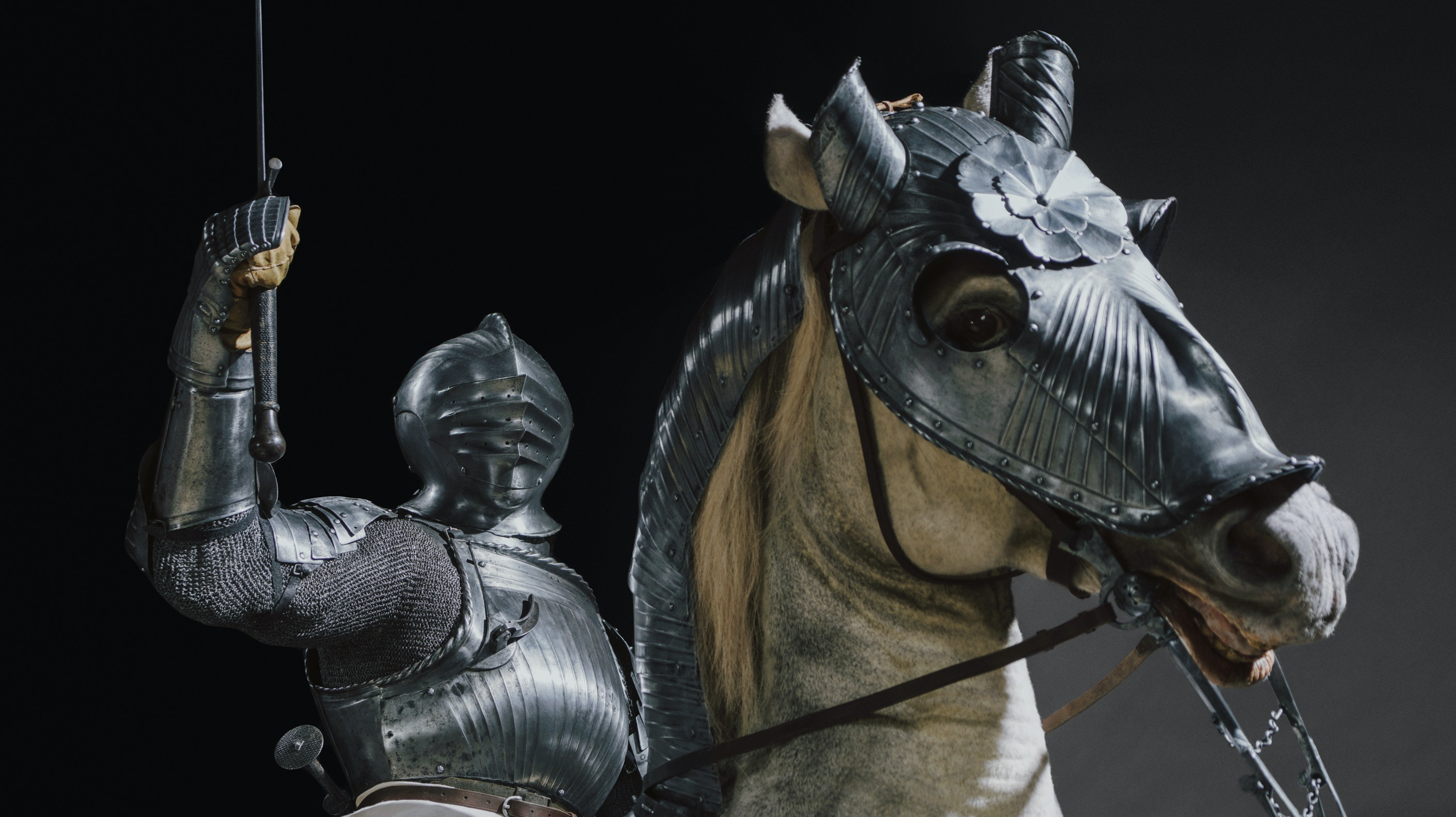 A man in a suit of armor sits atop of a rearing armored horse his lance drawn above his head.