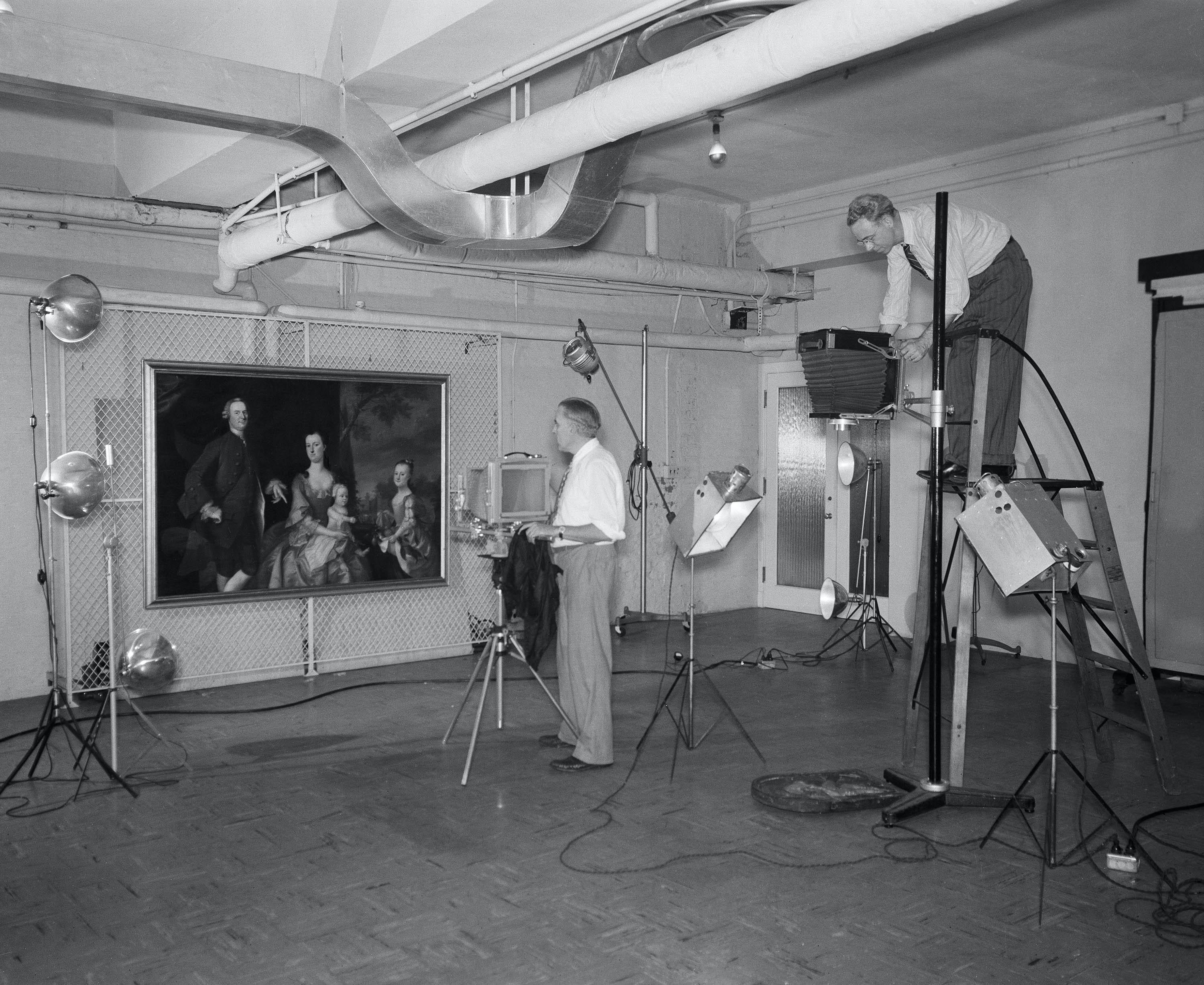 Old photo of staff photographers photographing art
