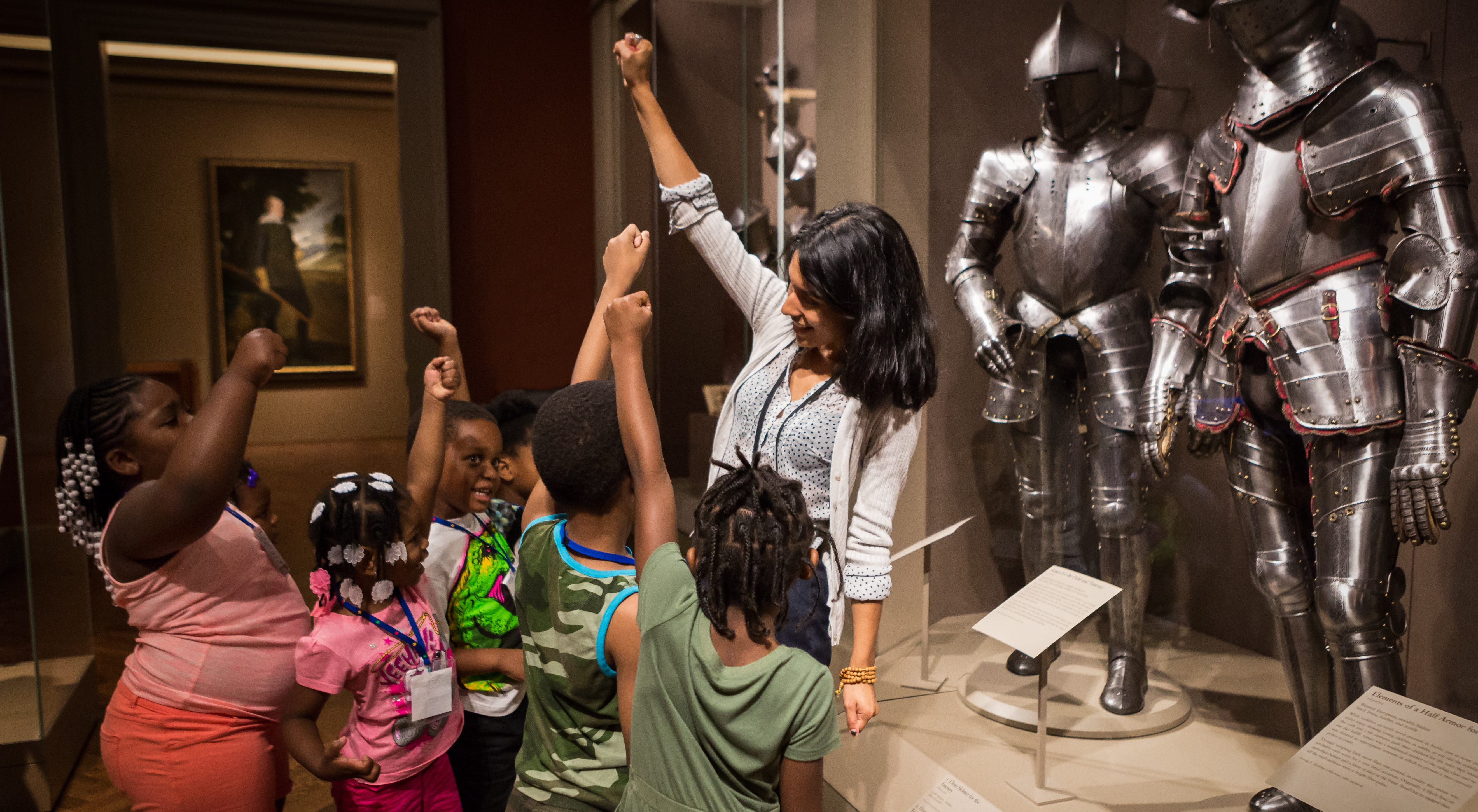 A group of students interact with a docent in front of two suits of armor in the galleries