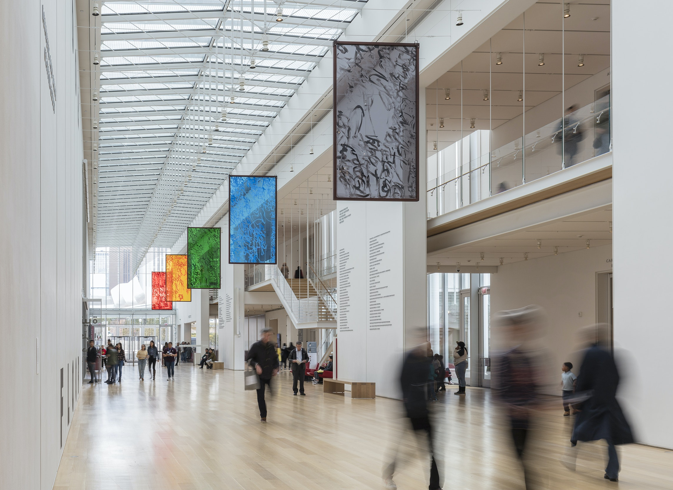 A photo of a installation of colored glass panels hanging over Griffin Court, a large open space in the museum. People walk underneath the panels.