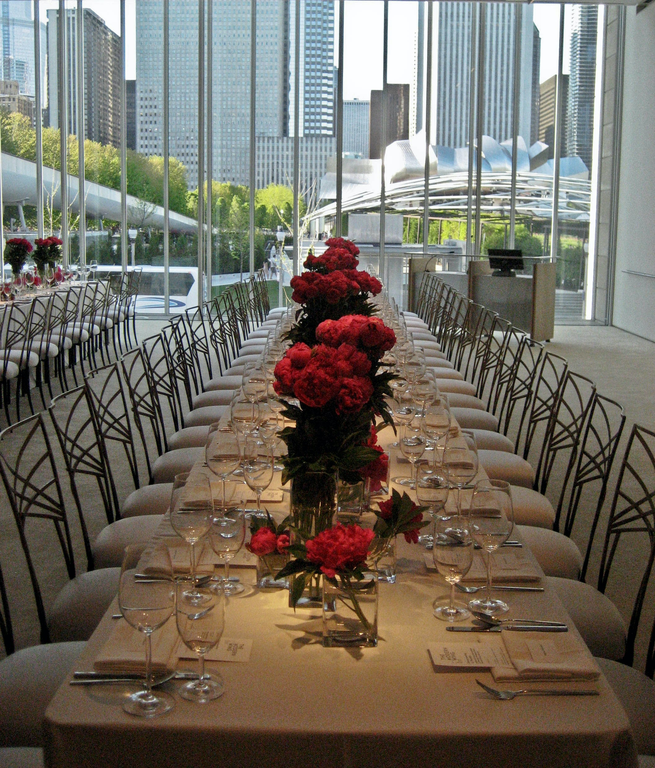 An image of a long set table with red flowers on it overlooking the city of Chicago