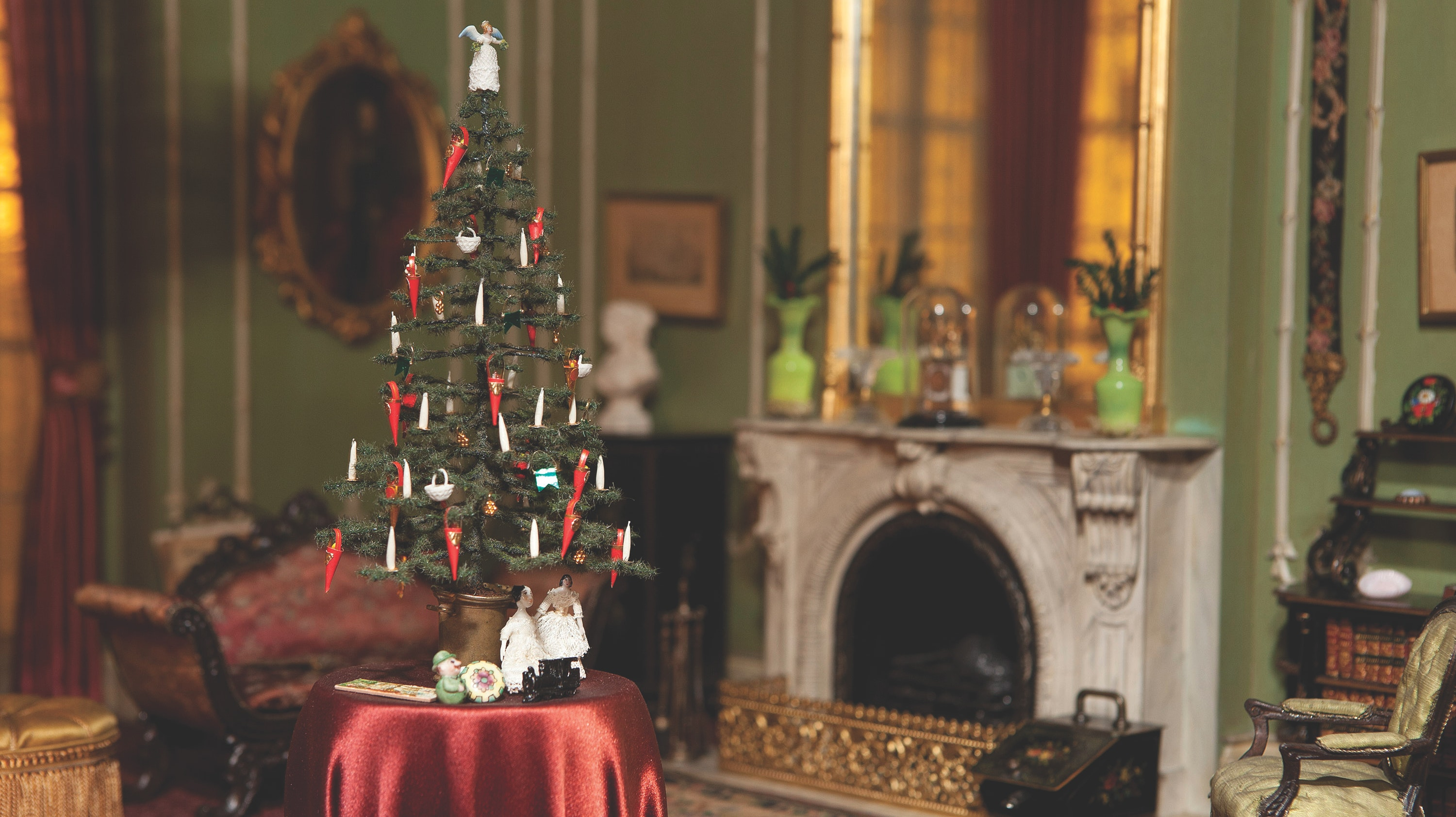 A photo of the Victorian Thorne Room decorated for the holidays. A small Christmas tree on a table covered in a red cloth is at the center of the image.