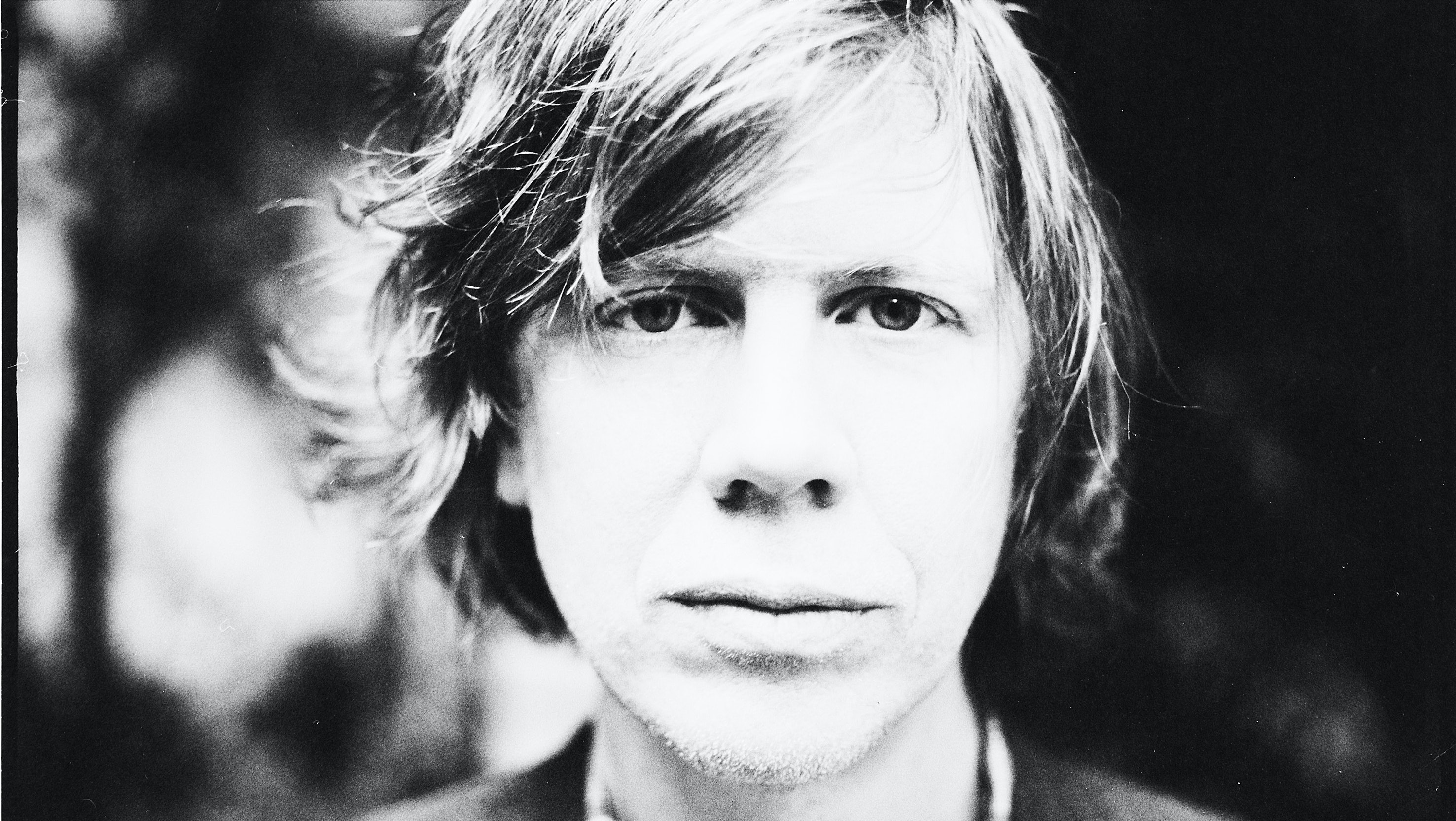 A black and white photo of Thurston Moore.