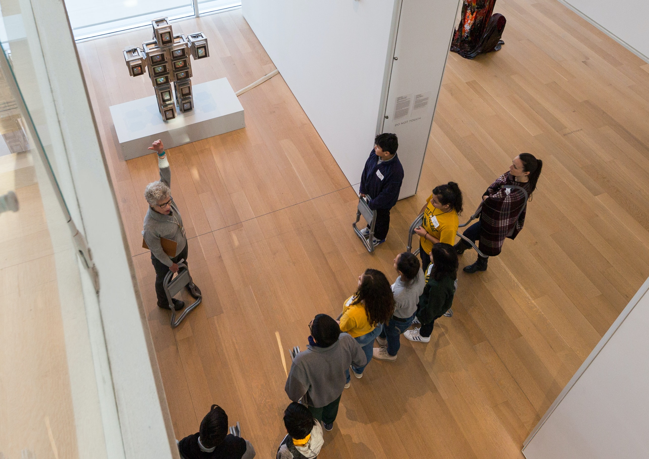 A docent speaks to a piece of contemporary artwork to a group of high school students on a museum tour