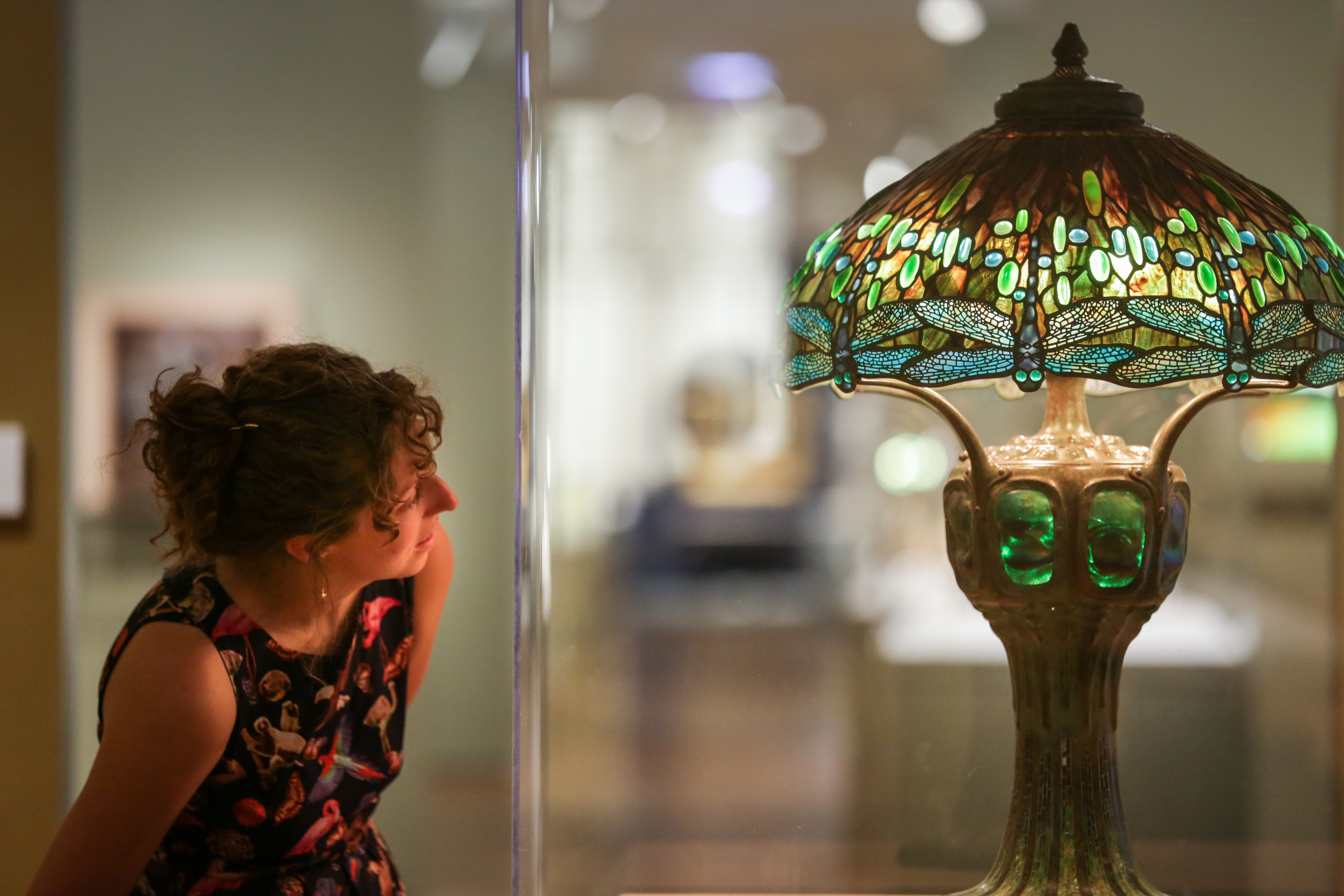 A woman looks at a stained glass lamp