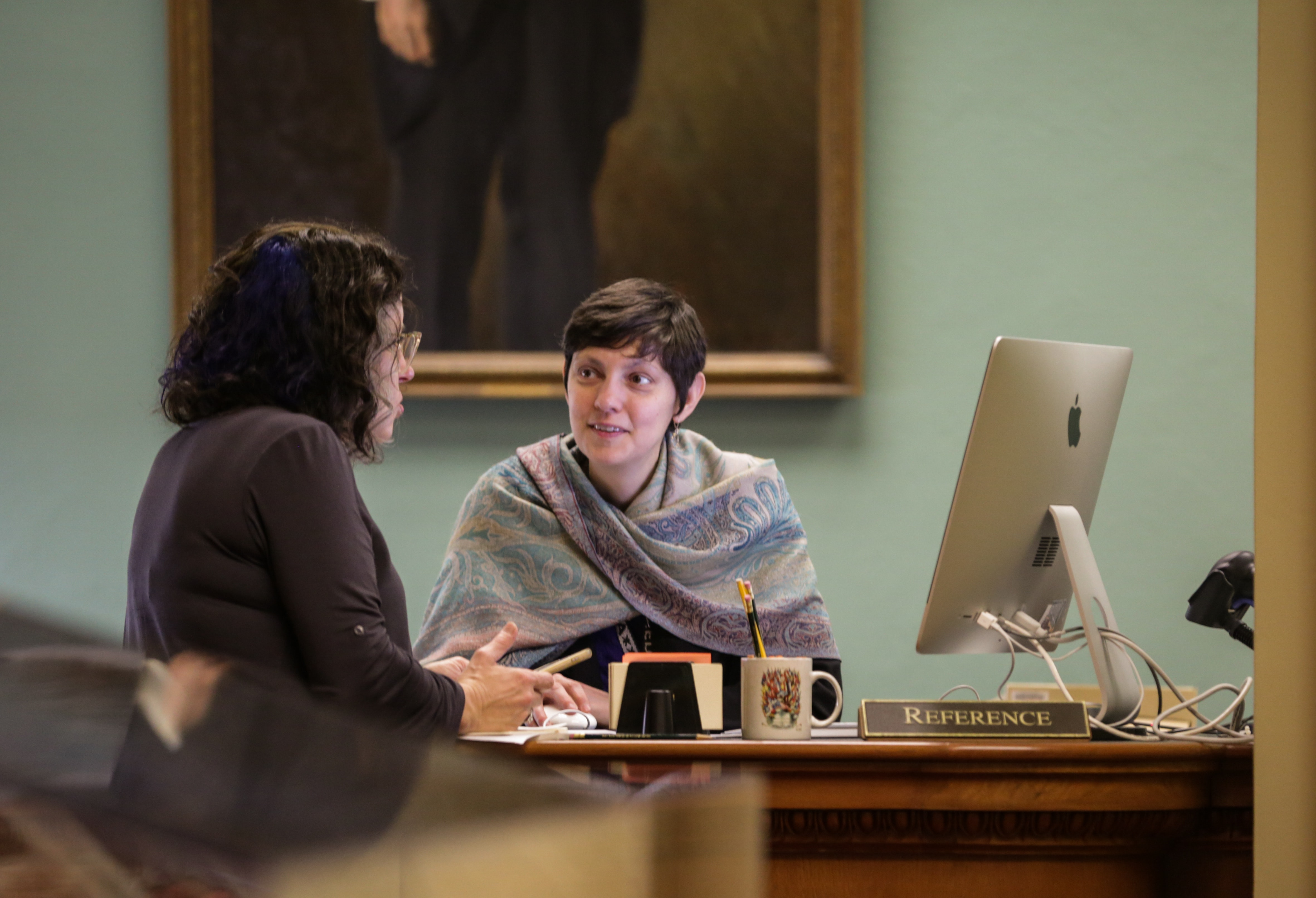 Image of two women at a desk, one sitting at a computer