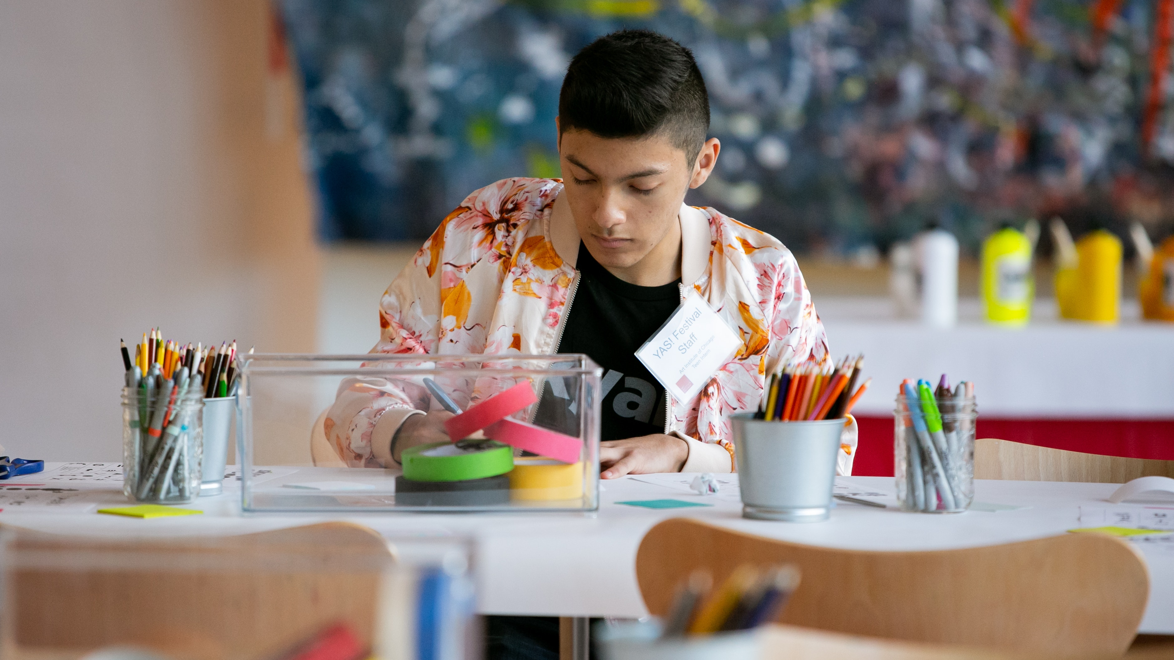 A photo of a teen making art at a table