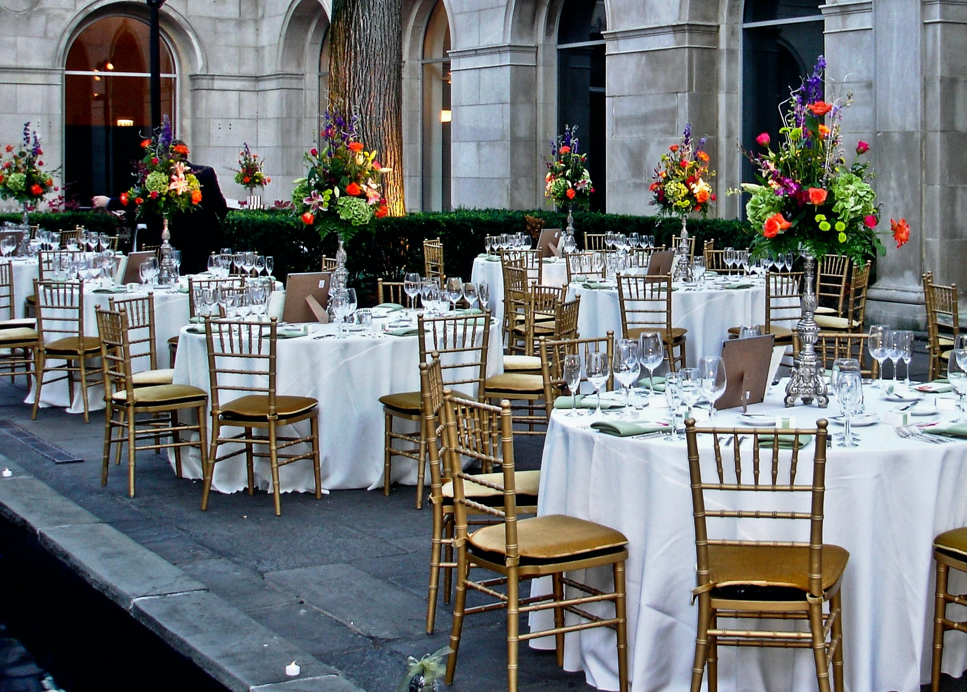 Tables with gold chairs and white table clothes are set outside in a marble court