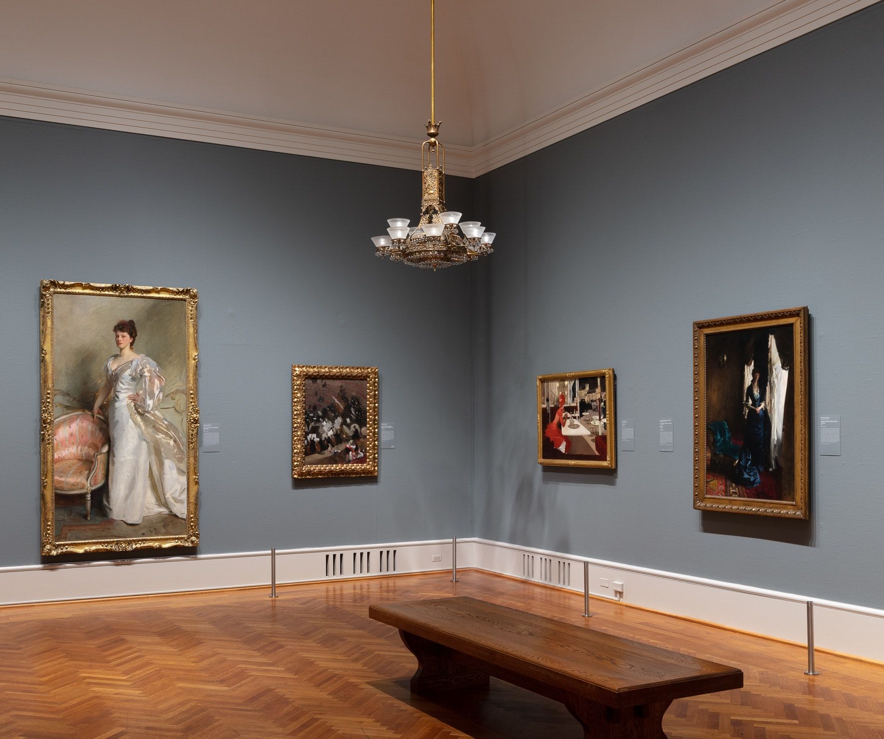 Photo showing a corner of the newly reinstalled gallery of American art, gallery 273, which features a gasolier and paintings by John Singer Sargent