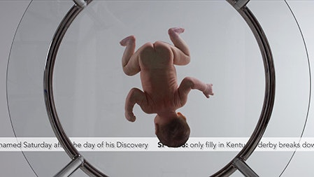 A still from a film depicting an upside-down baby in a circle.