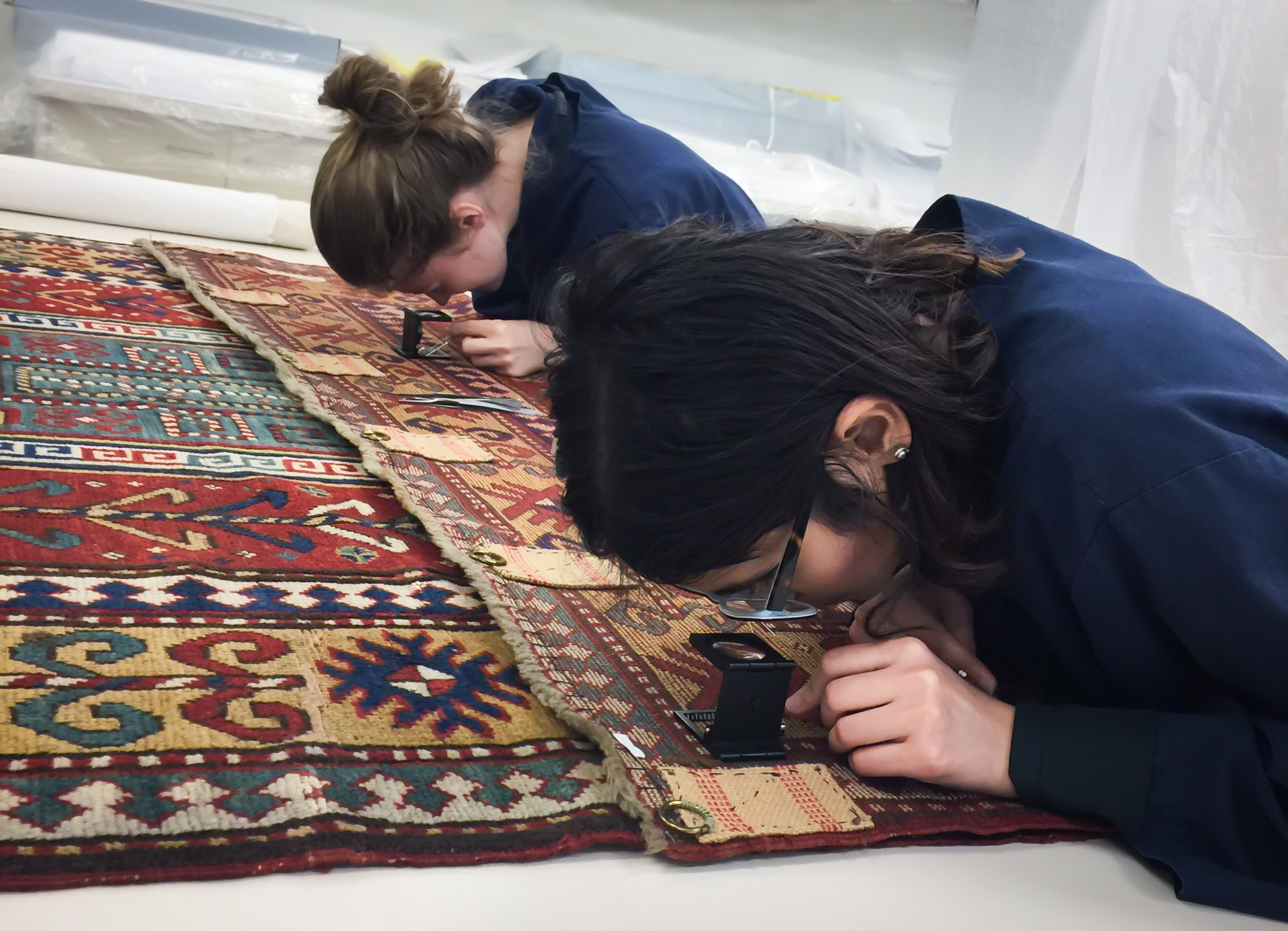 Two conservators work closely on a rug