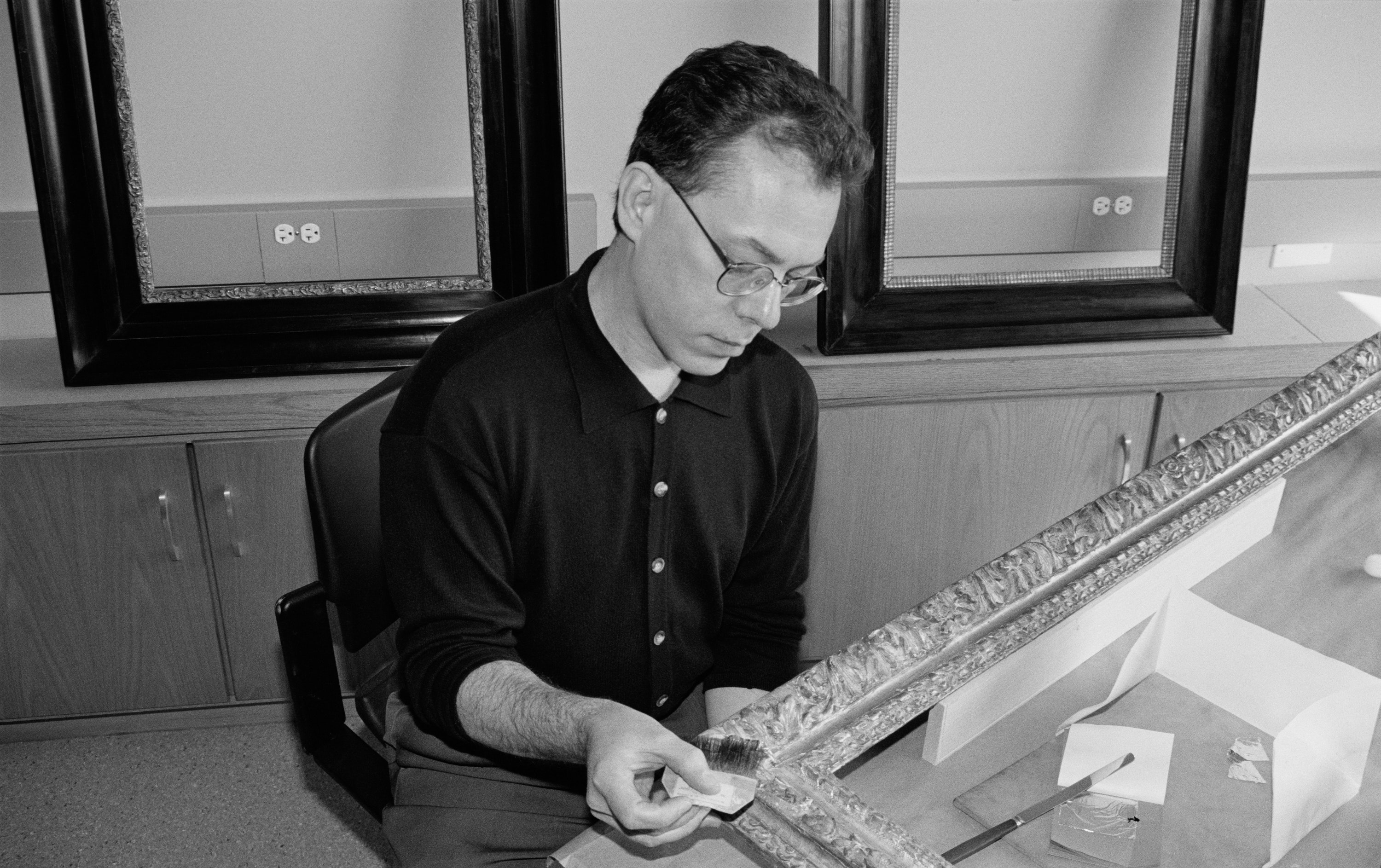 a frame conservator uses a cotton ball on a frame.