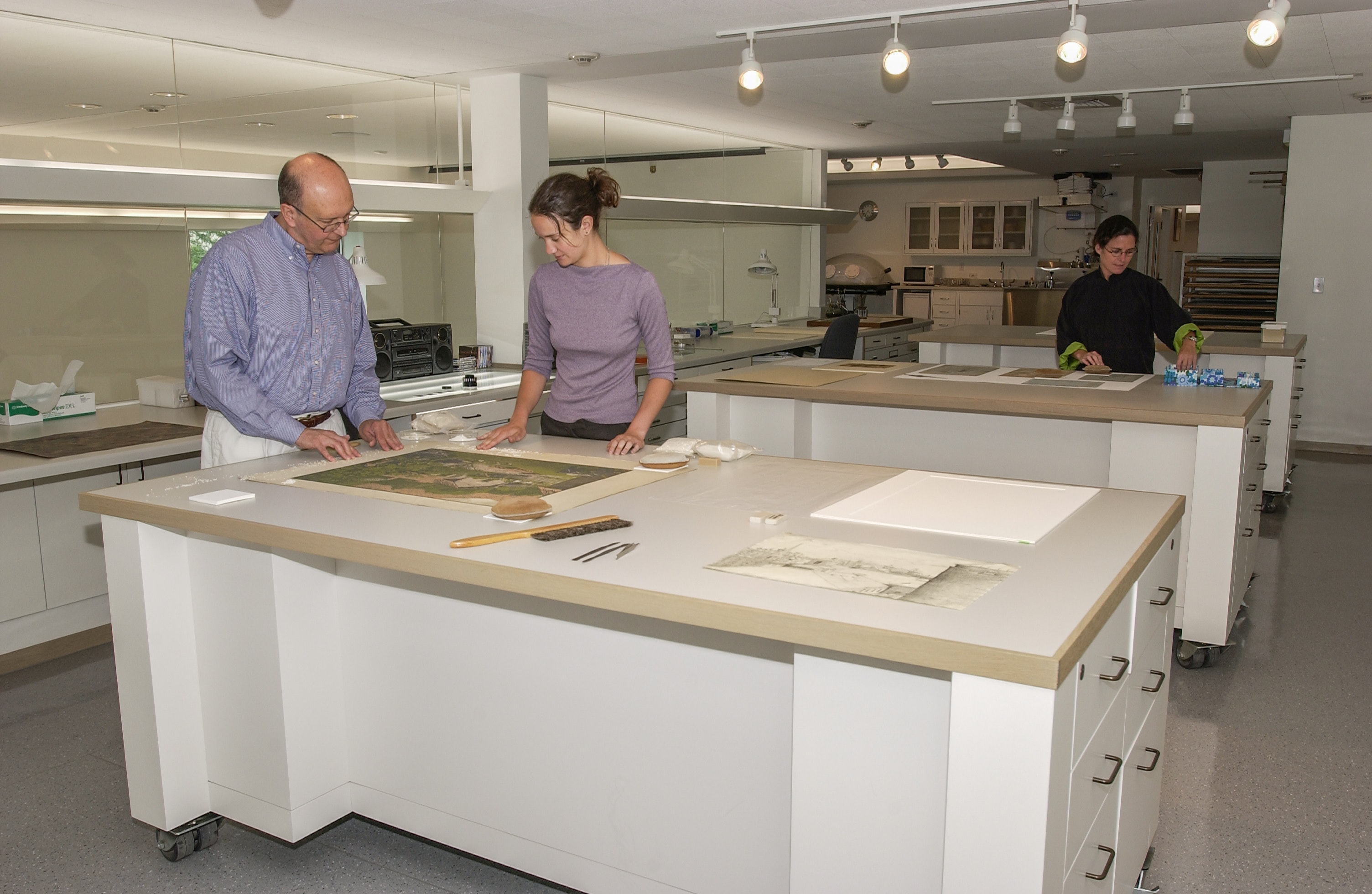 Two paper conservators review a piece of artwork