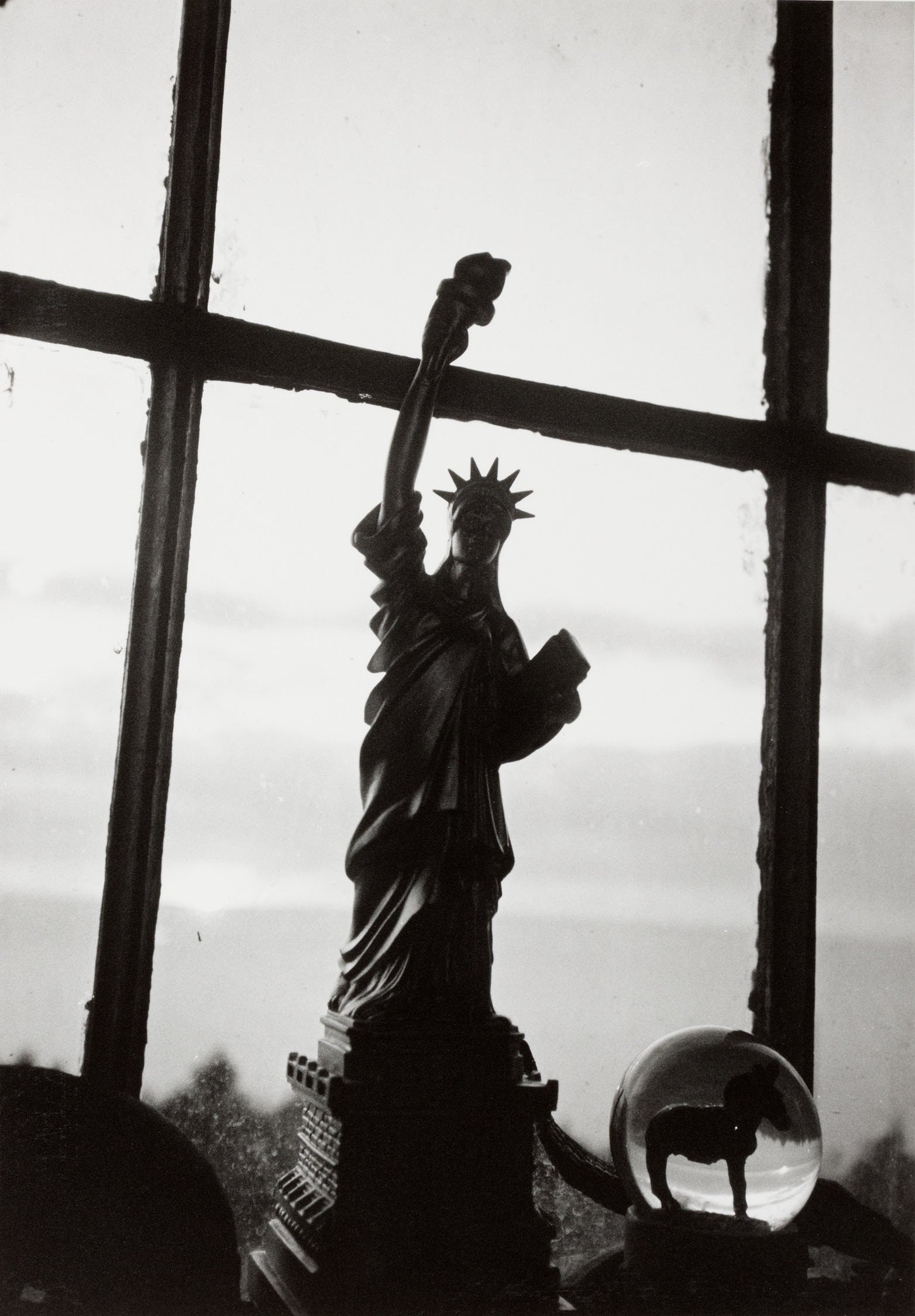 A black and white photo of a small figurine of the Statue of Liberty in front of a window.