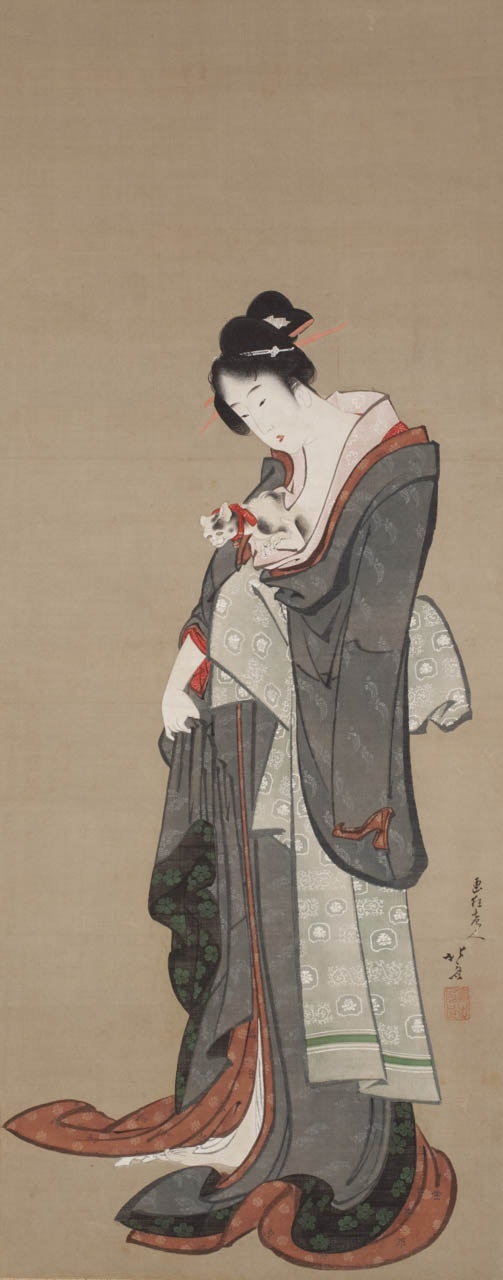 A Japanese woman in long flowing robes stands caressing a cat.