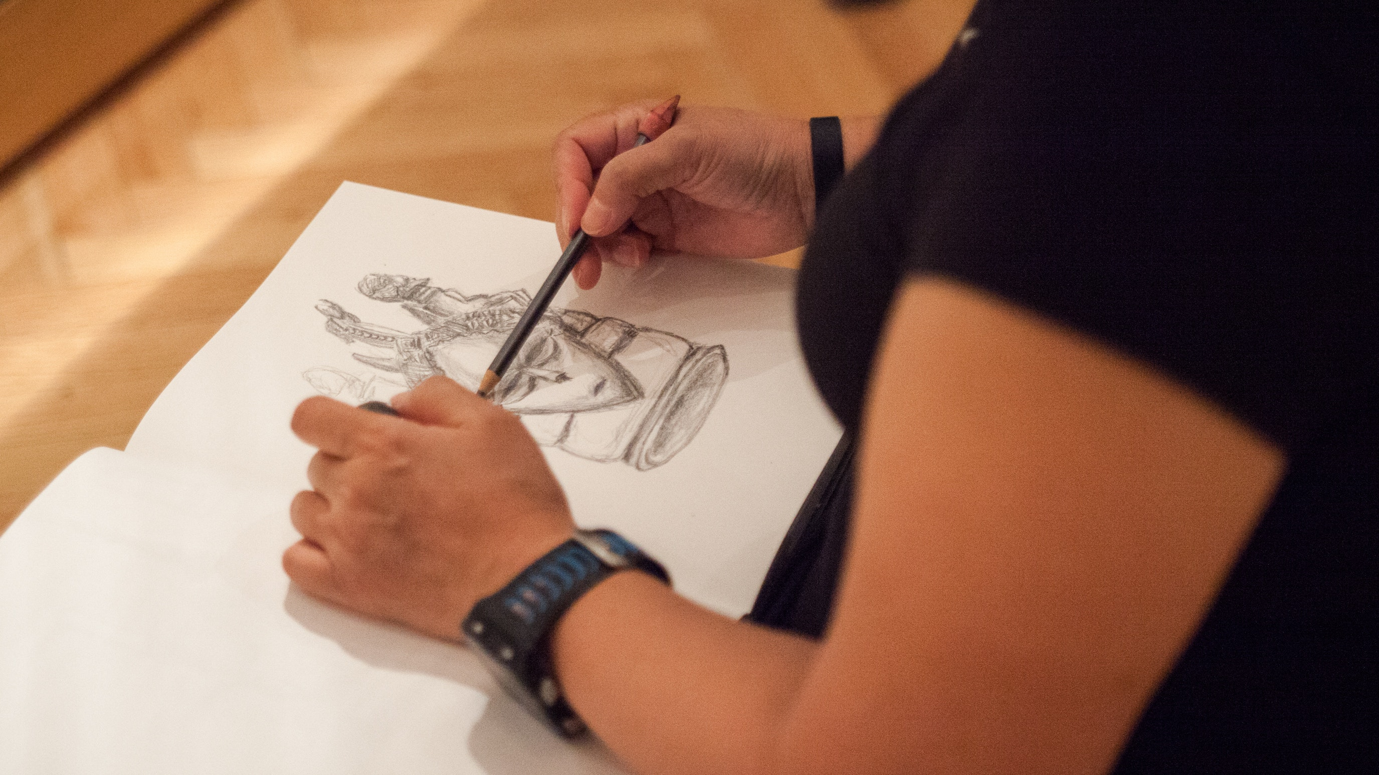 Person drawing an object from the collection in a sketchbook