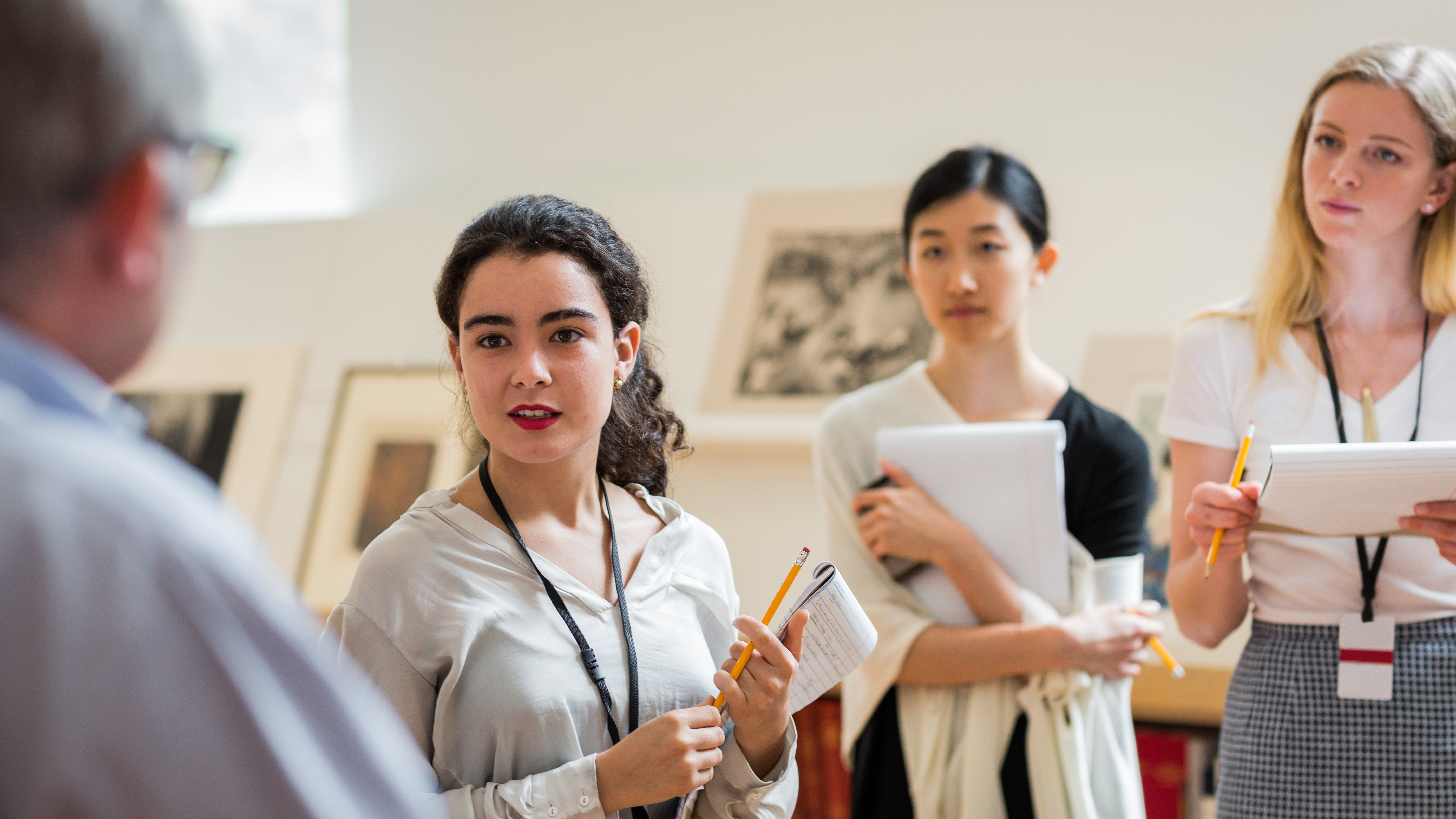 A group of students listens to a curator speak