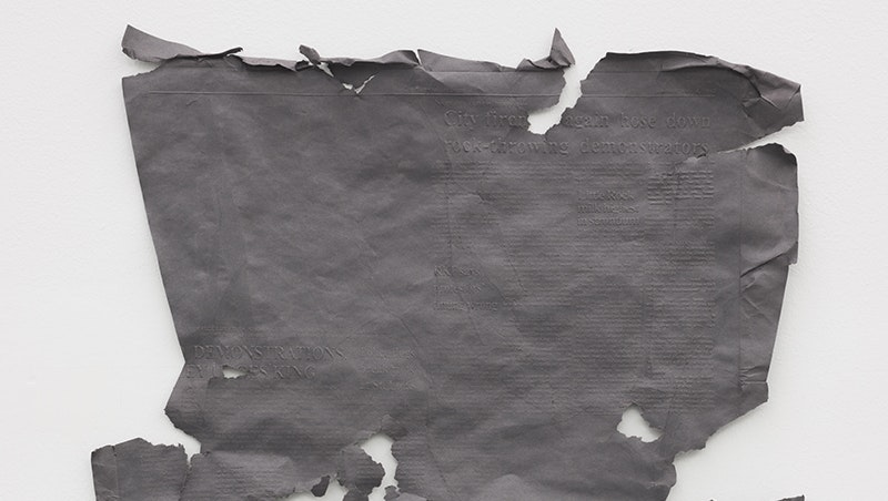 A gray piece of tattered fabric is hung on a white wall.