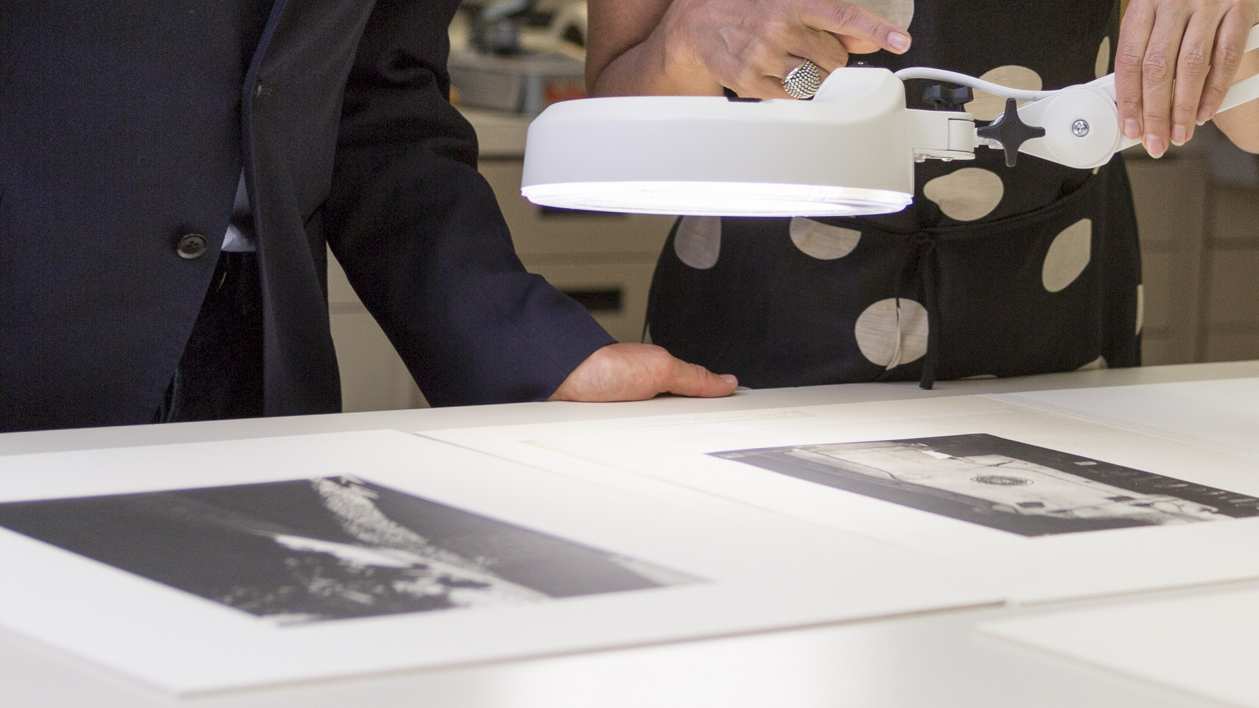 A curator and a conservator examine at two phtographs through a magnifying lamp.