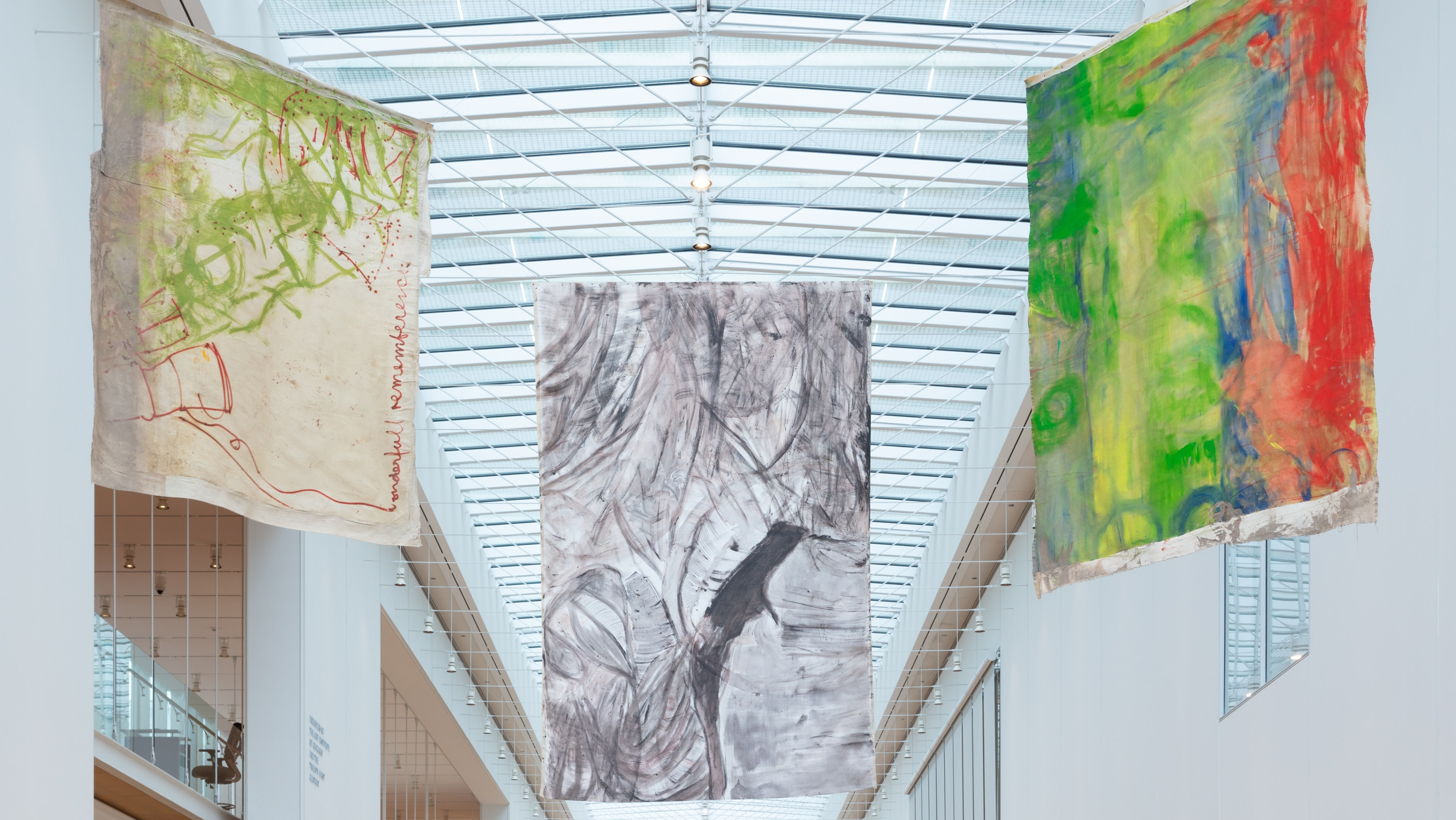 Three paintings on unstretched canvas hang from the ceiling in the museum's Griffin Court.
