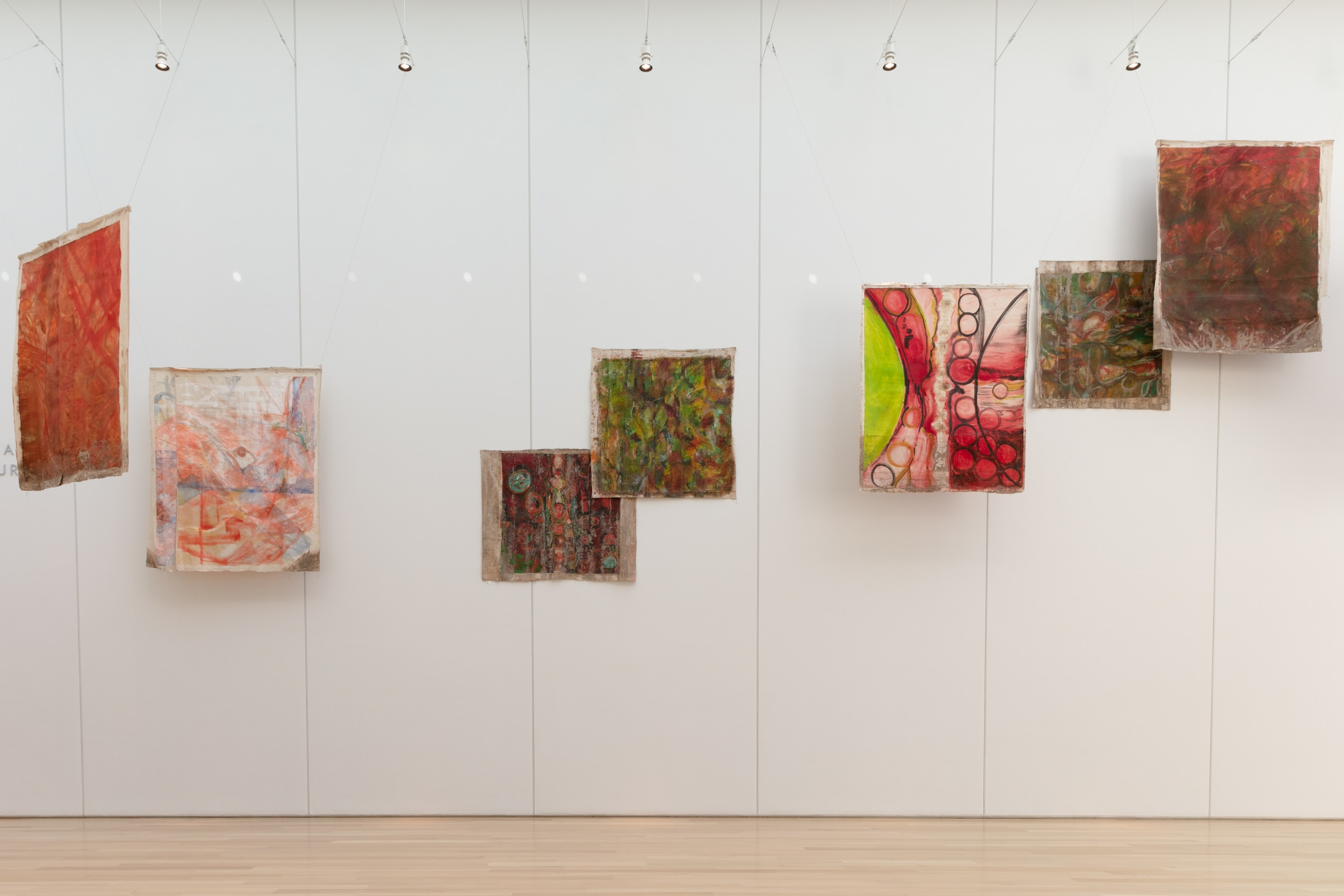 Various paintings on unstretched canvas are suspended and overlap in their installation in the museum's Griffin Court