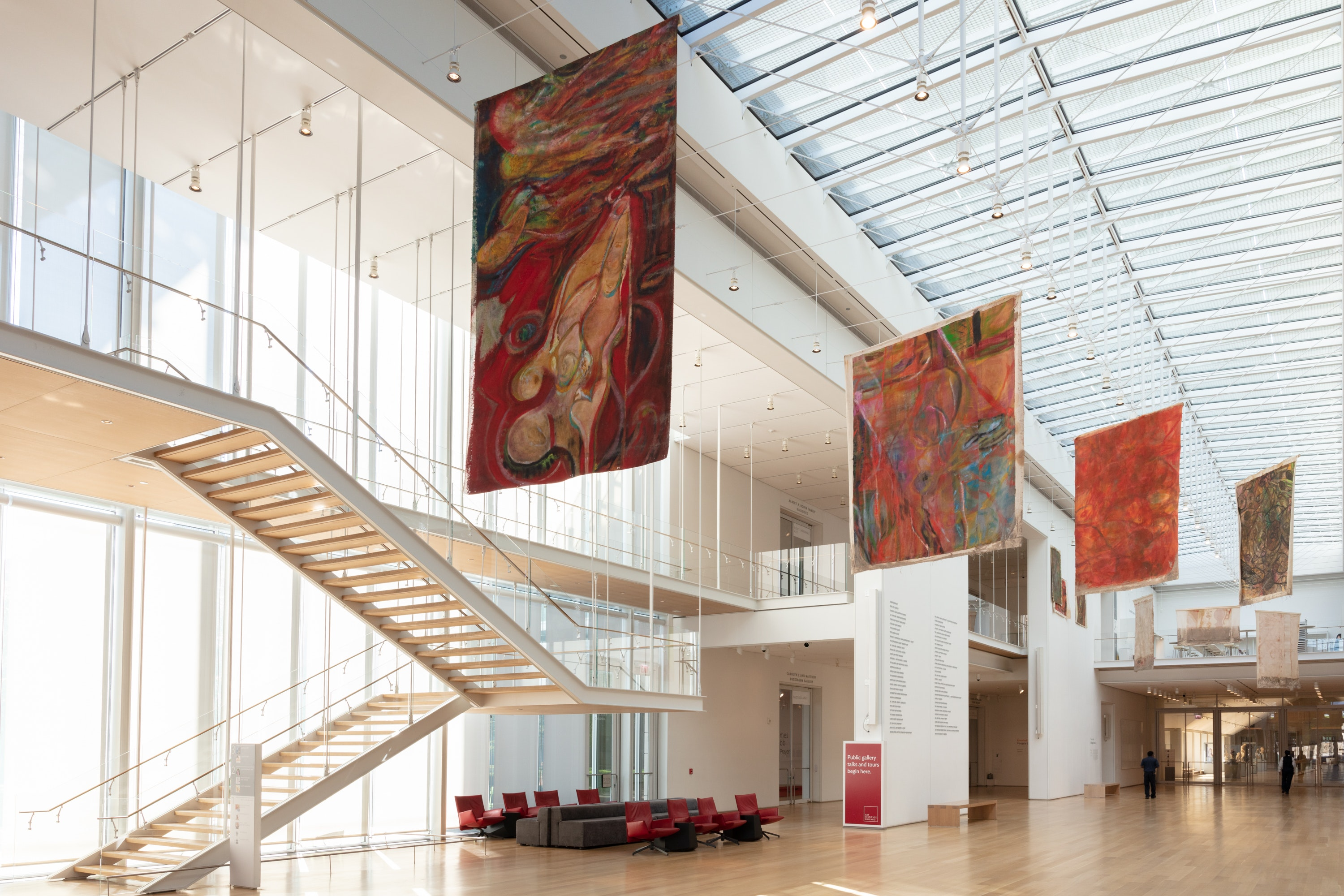Various paintings on unstretched canvas hang from the ceiling in the museum's Griffin Court