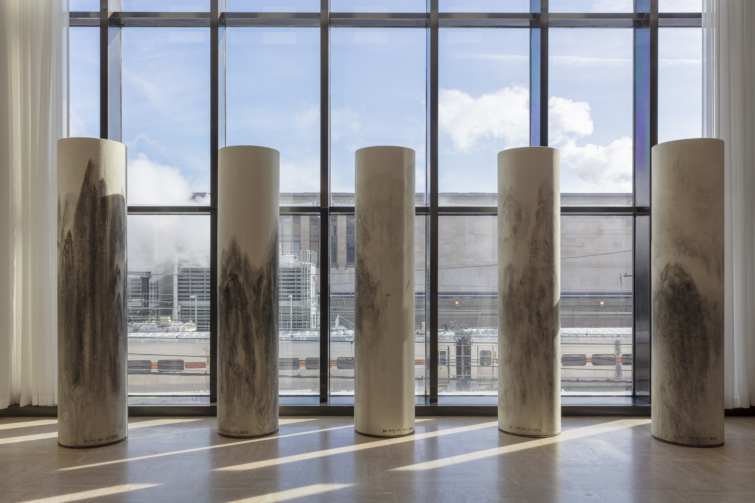 A photo of an installation of five large white columns painted with black ink in front of a large, sunlit window.