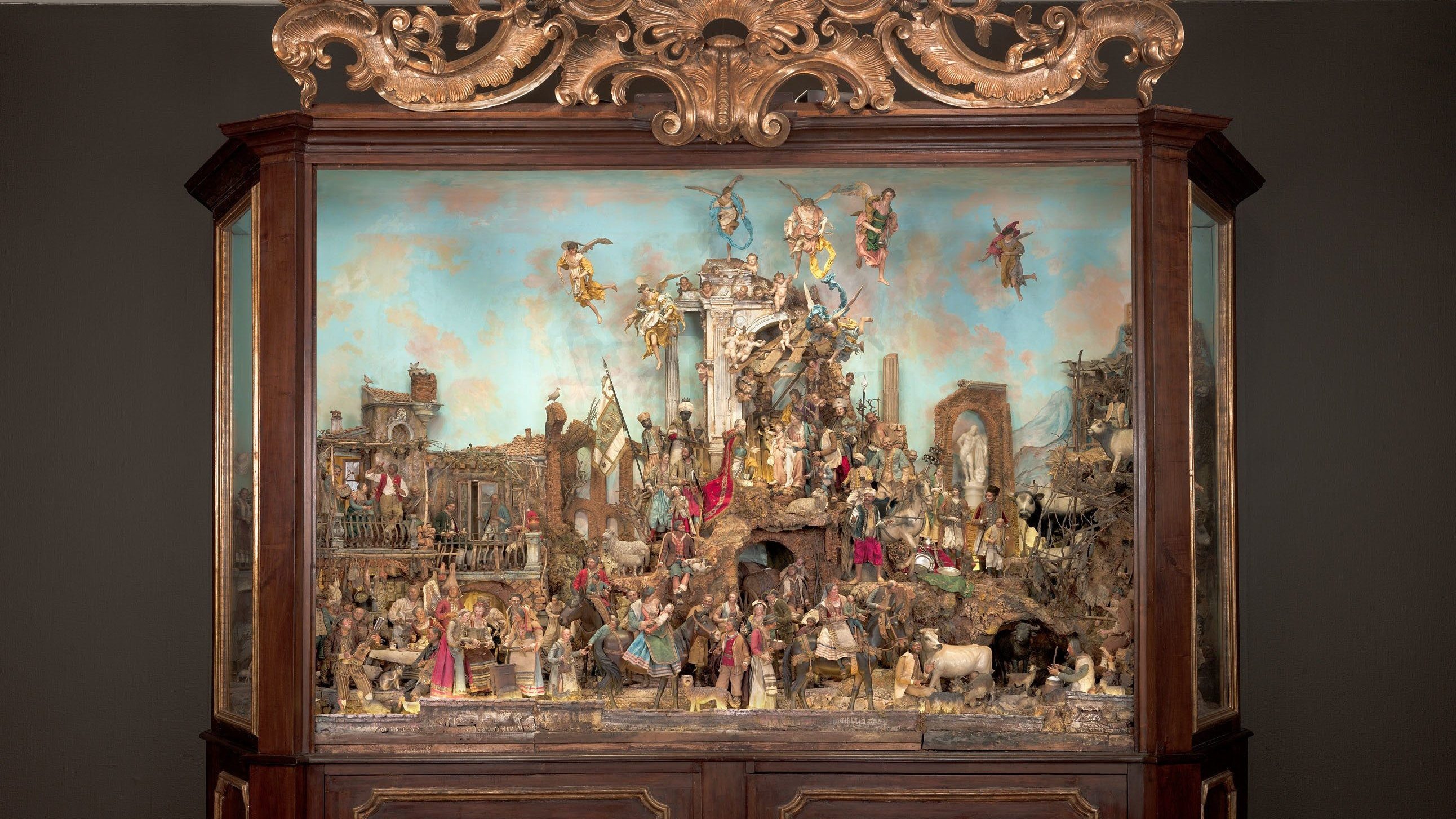 A photo of a large Neapolitan Creche made up of small, elaborate figures in a dark wooden ornamented case.