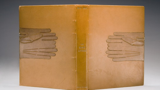 Tan leather cover of a book with matching leather gloves where you would hold a book.