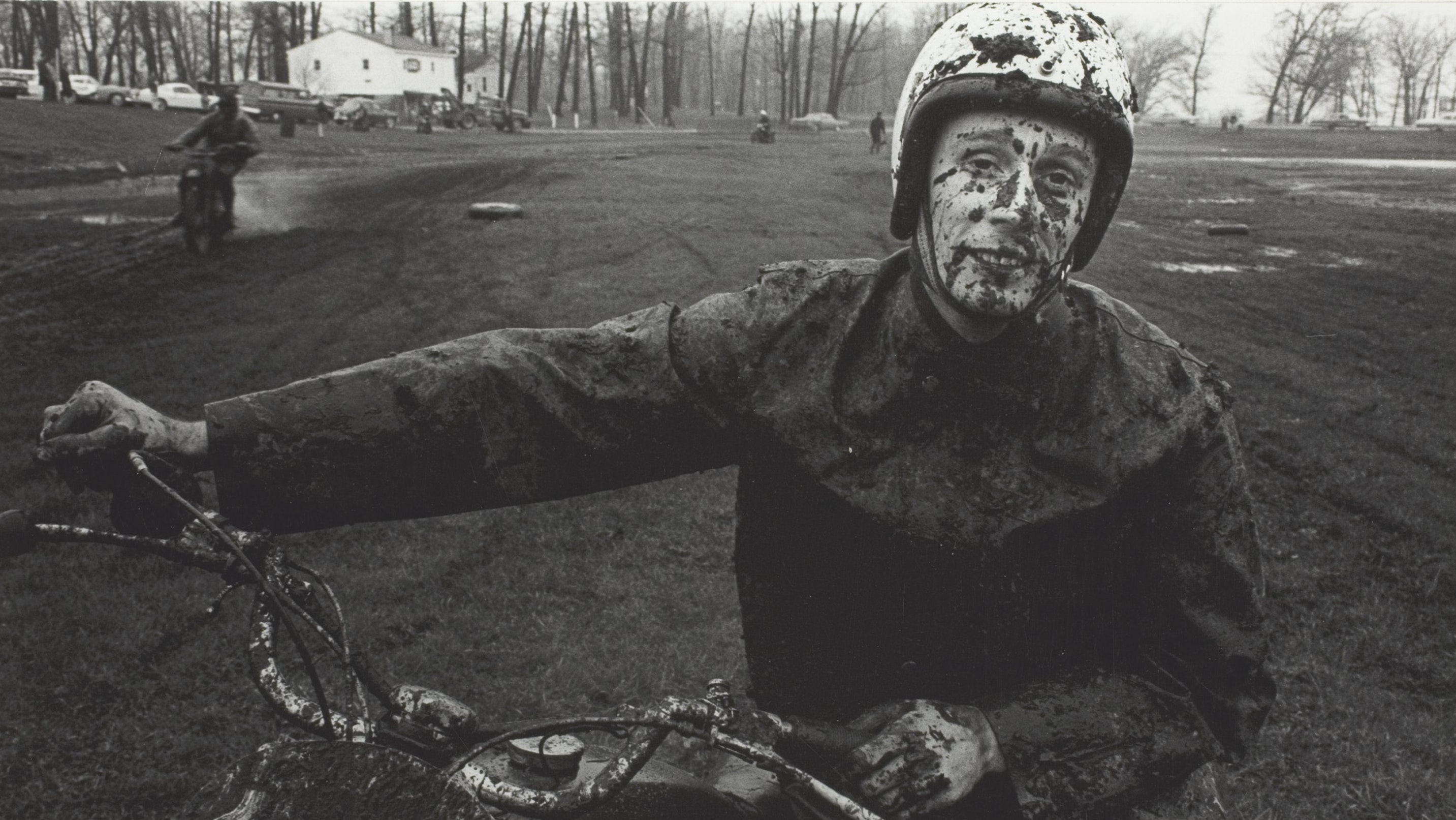 A photo of a man on a motorcycle with his face, hands, and clothes spattered with mud.