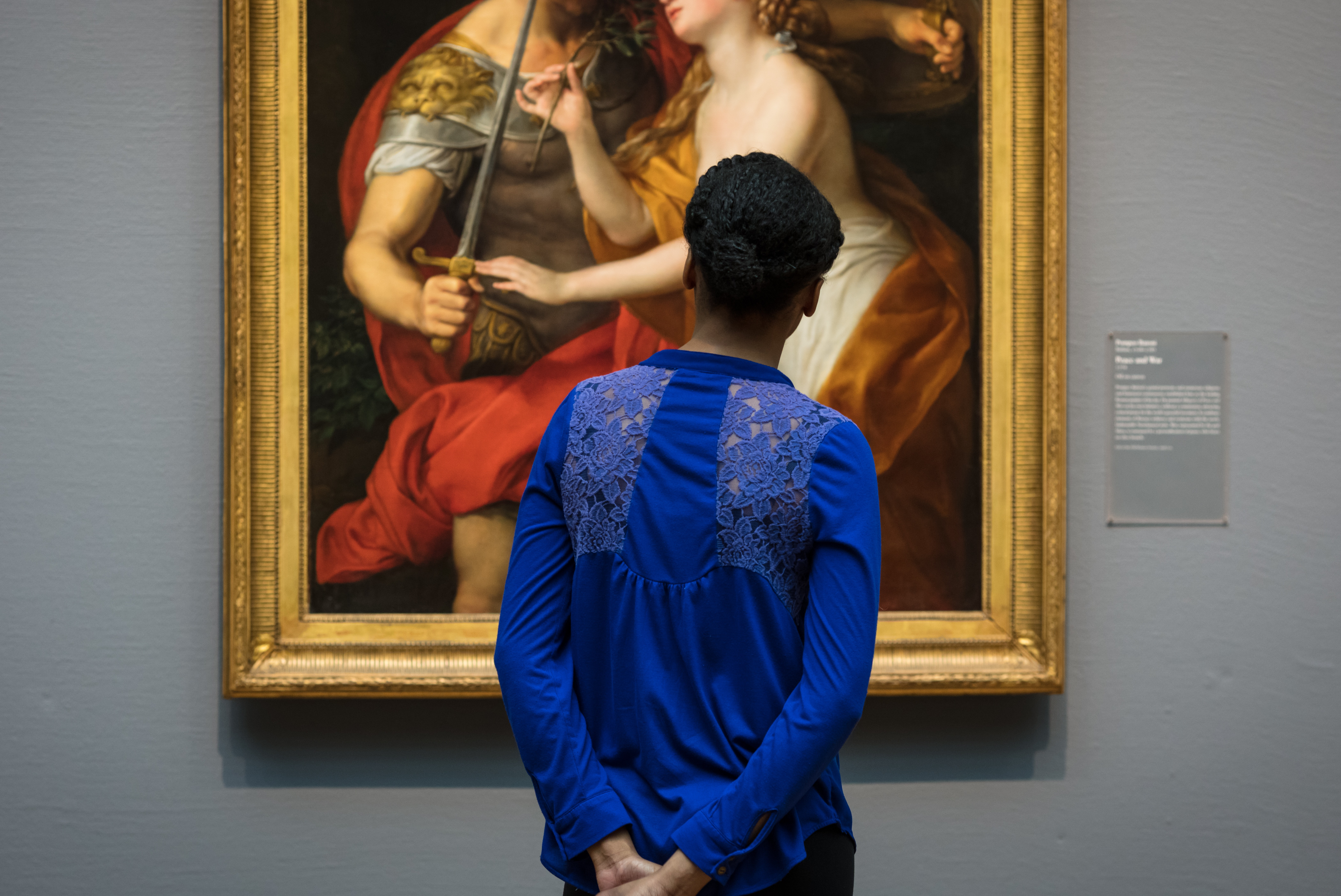 A woman stands in front of a Renaissance painting